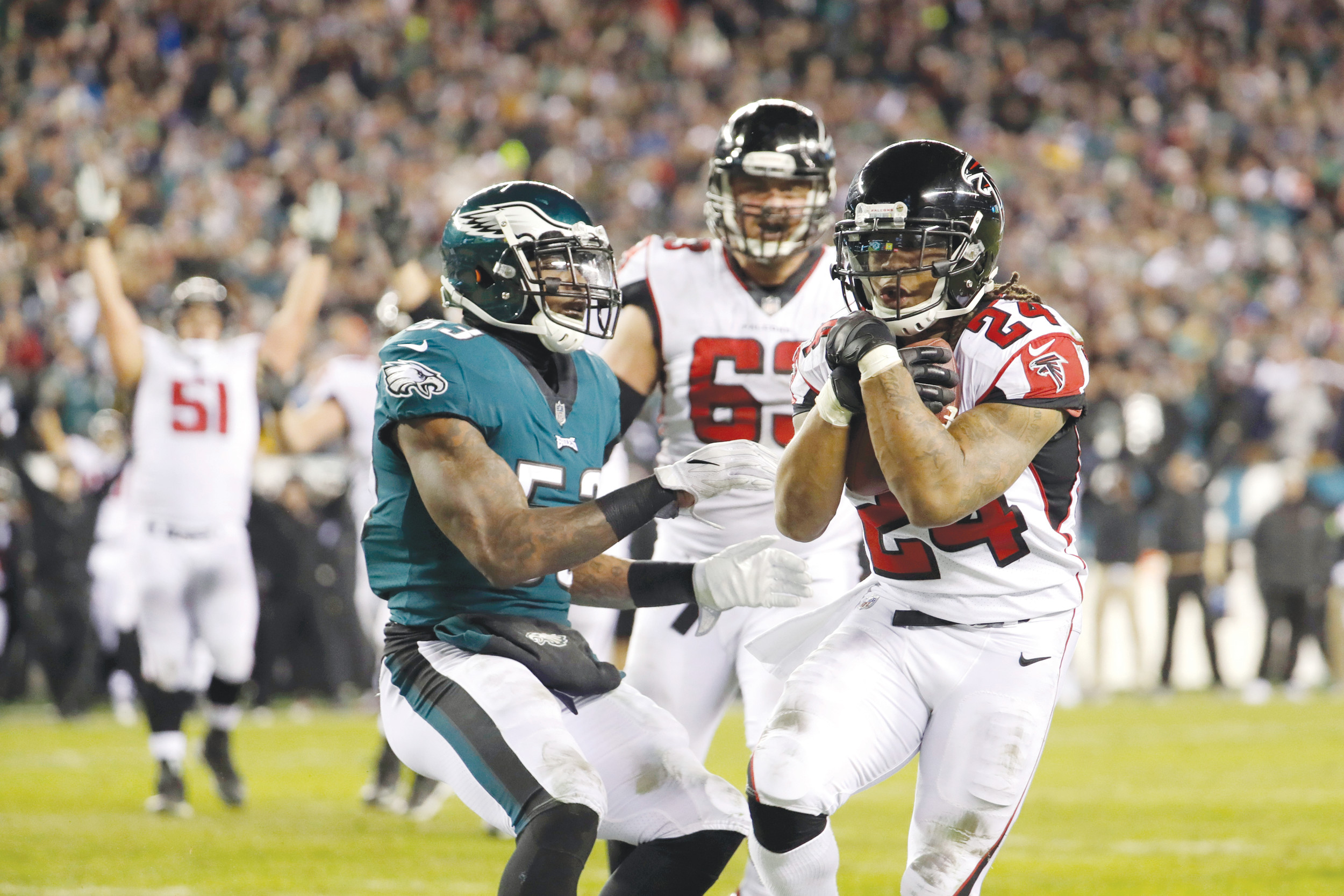Atlanta running back Devonta Freeman (24) scores a touchdown against Philadelphia linebacker Nigel Bradham (53) during the first half of the Eagles' 15-10 victory in an NFC divisional playoff game on Saturday in Philadelphia.