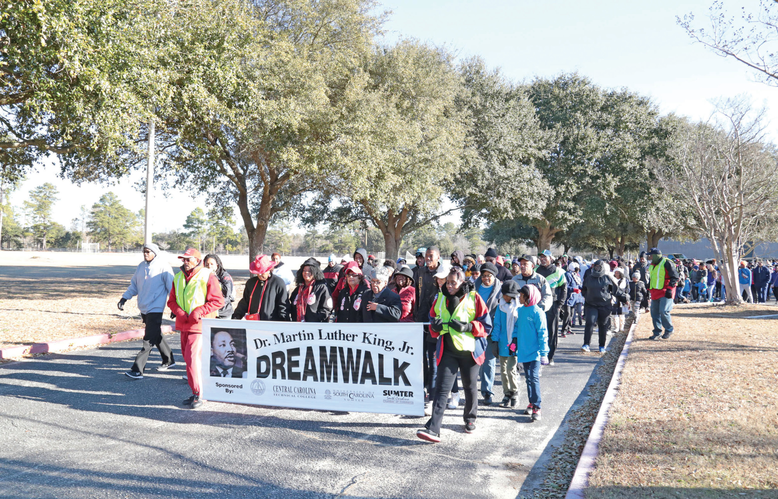 Attendees lead the 18th Annual Dr. Martin Luther King Jr. Dream Walk at University of South Carolina Sumter on Monday morning. More than 400 people participated in the event, according to college officials.