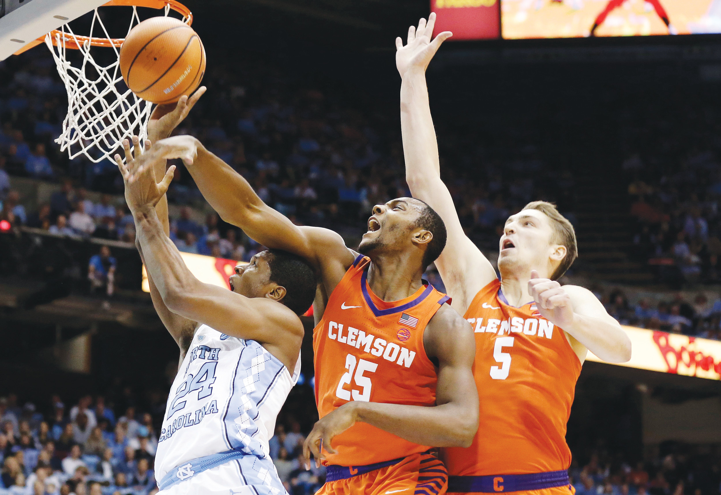 North Carolina's Kenny Williams (24) drives to the basket against Clemson's Aamir Simms (25) and Mark Donnal (5) during the first half of the Tar Heels' 87-79 victory over the Tigers in Chapel Hill, North Carolina on Tuesday. UNC improved to 59-0 all-time at home against Clemson.