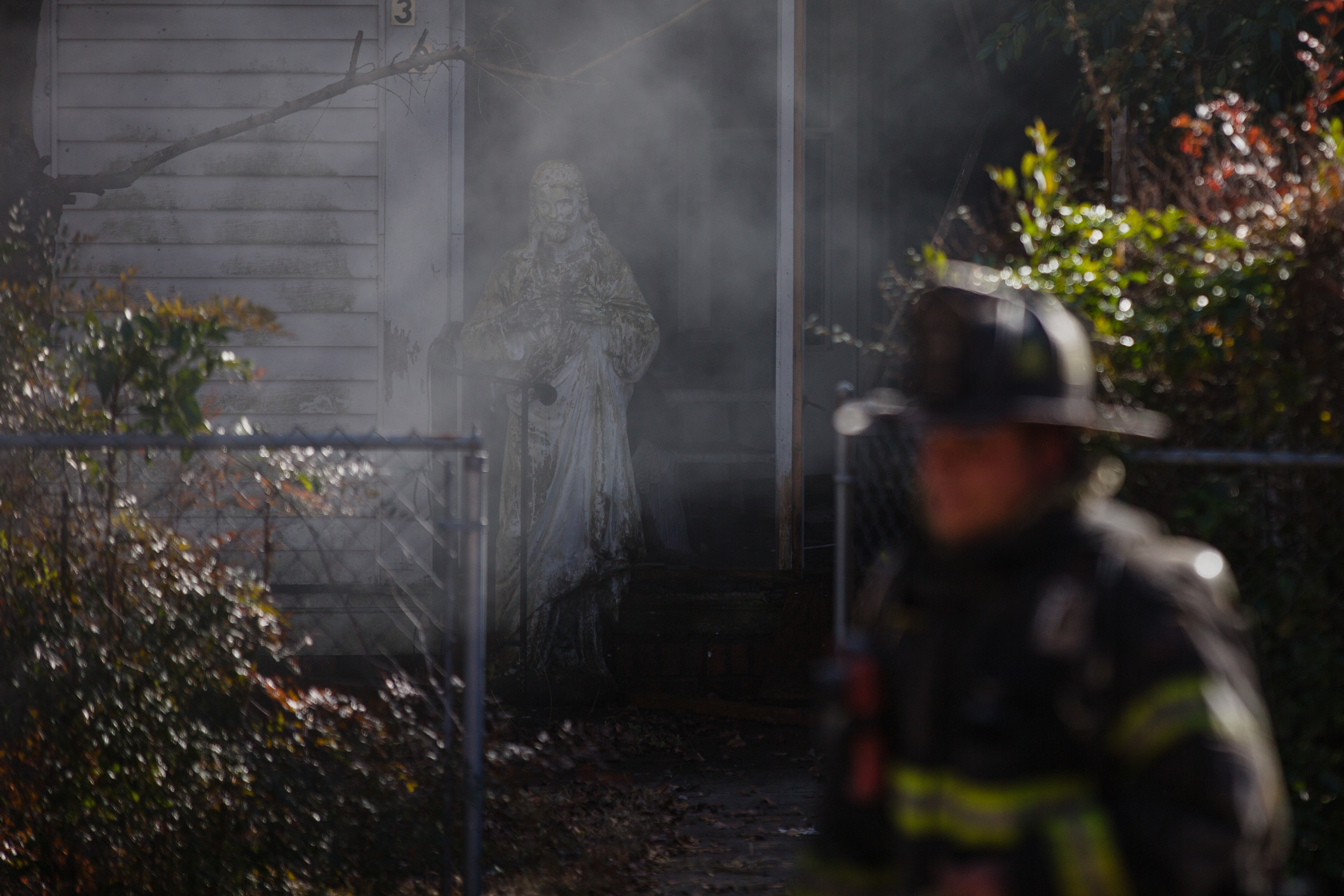 Firefighters work to fight back flames at a residential fire on McQueen St.