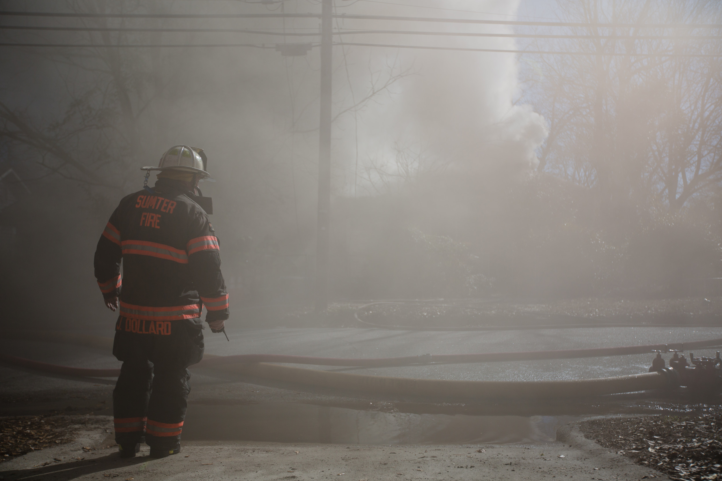 Firefighters work to fight back flames at a residential fire on McQueen Street.