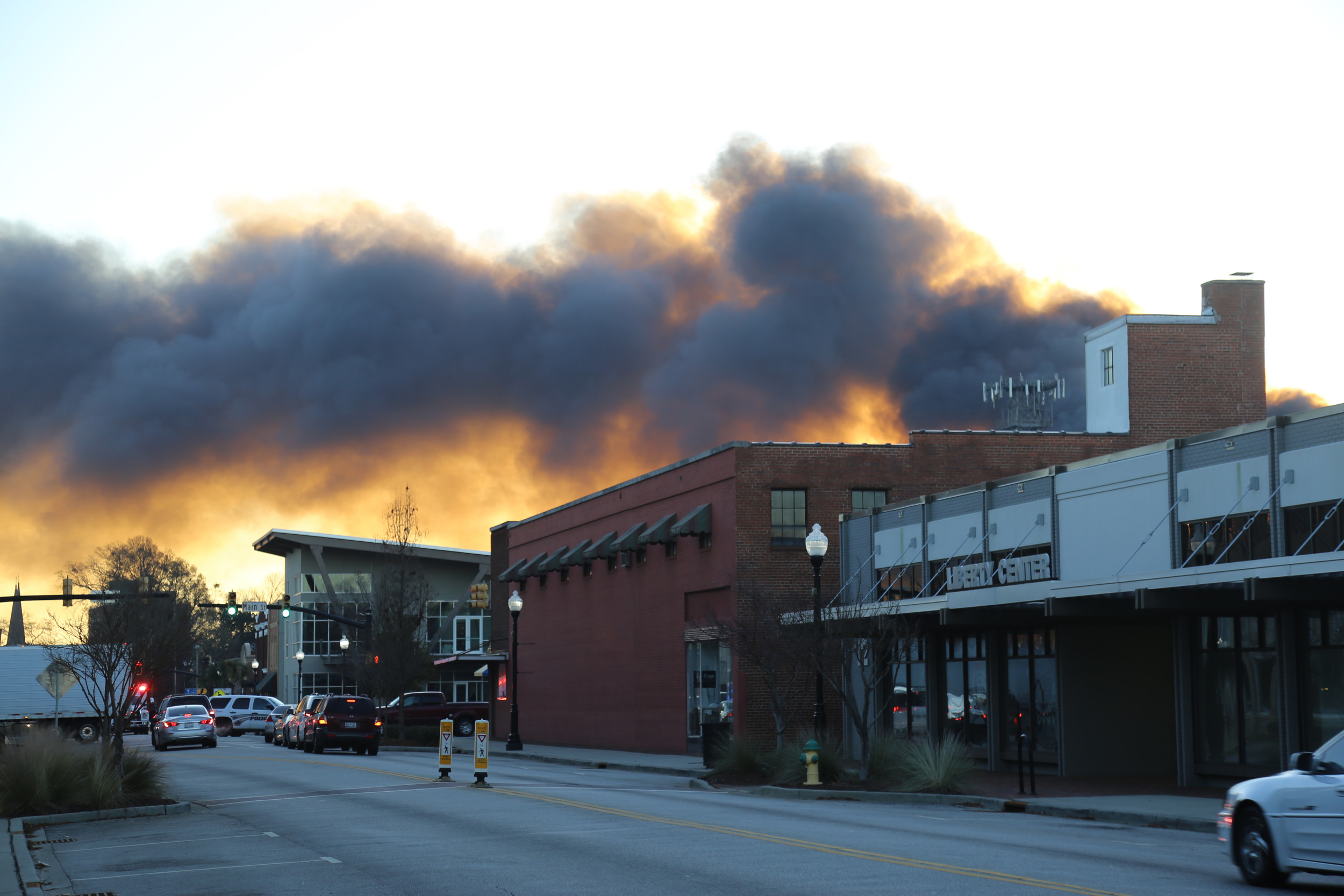 Light shines behind smoke looming over downtown Sumter Friday morning as it drifts north from Hauser Street.