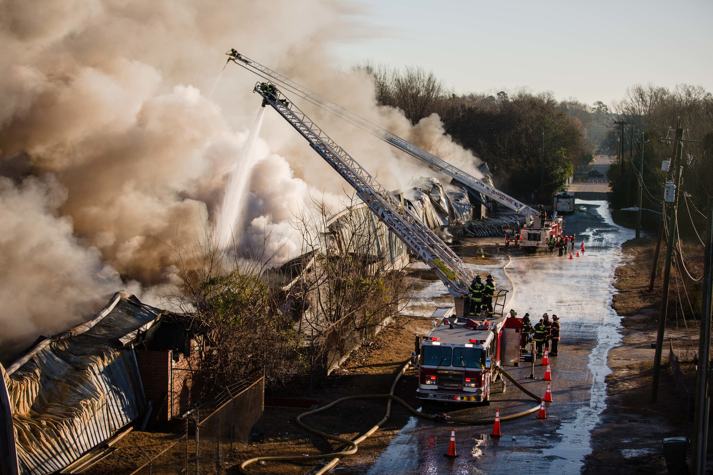 Firefighters dump water on a warehouse filled with carpet fibers and plastic Friday morning. A total of 90 firefighters worked the blaze throughout the day.