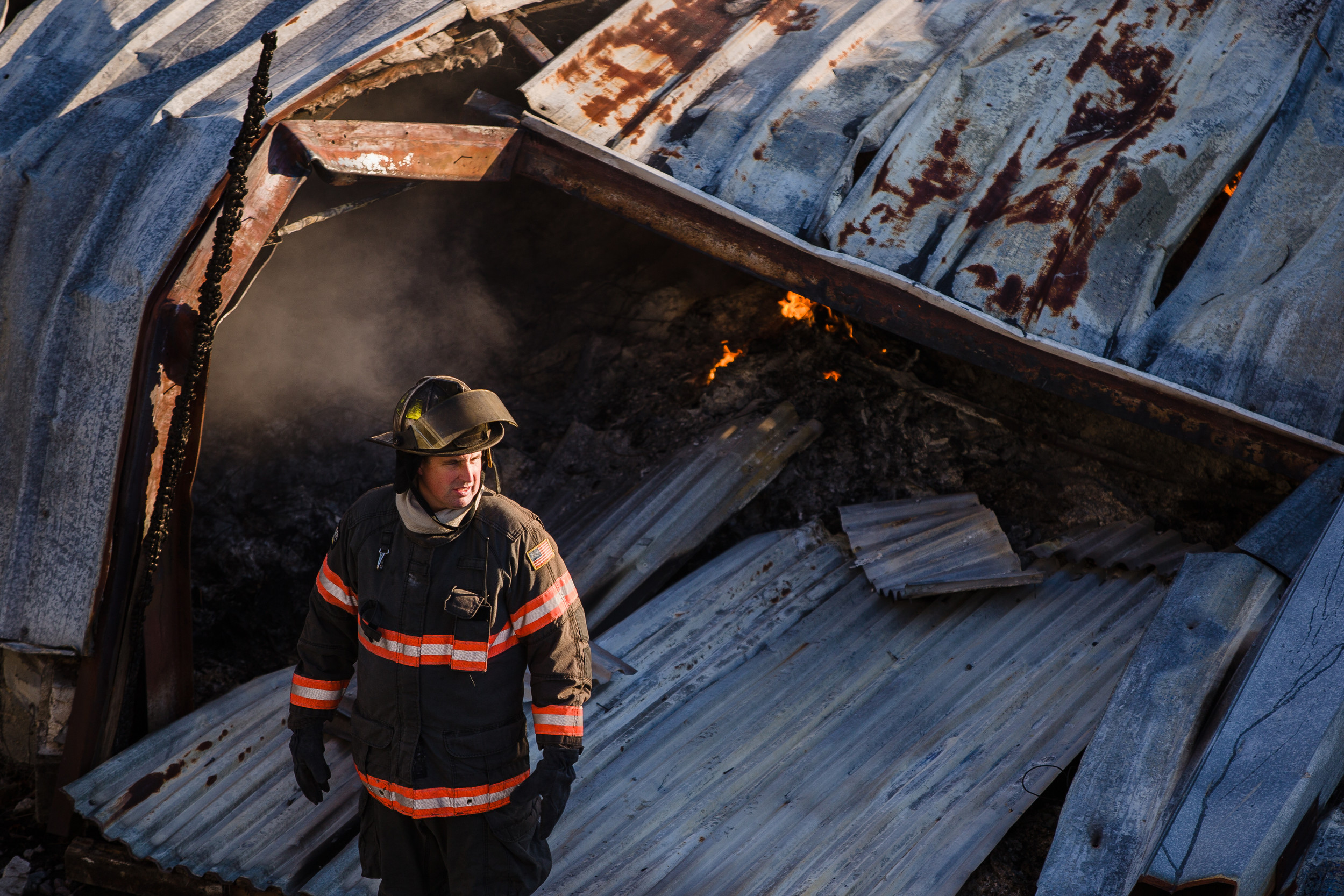 A firefighter stands near the blaze during the morning.