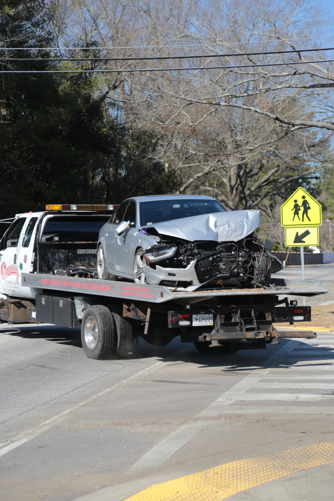 A tow truck from Carolina Collision Center carries the damaged sedan from the school property.