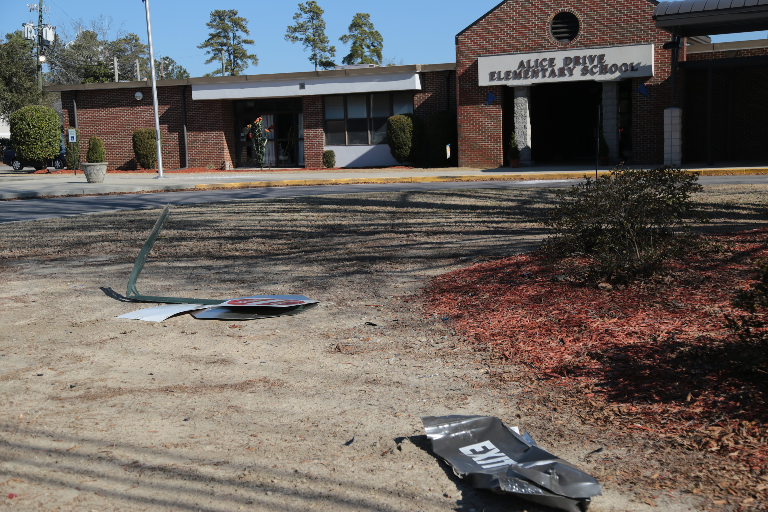 Two damaged road signs lay on the front grounds of the elementary school after they were knocked down during the wreck.