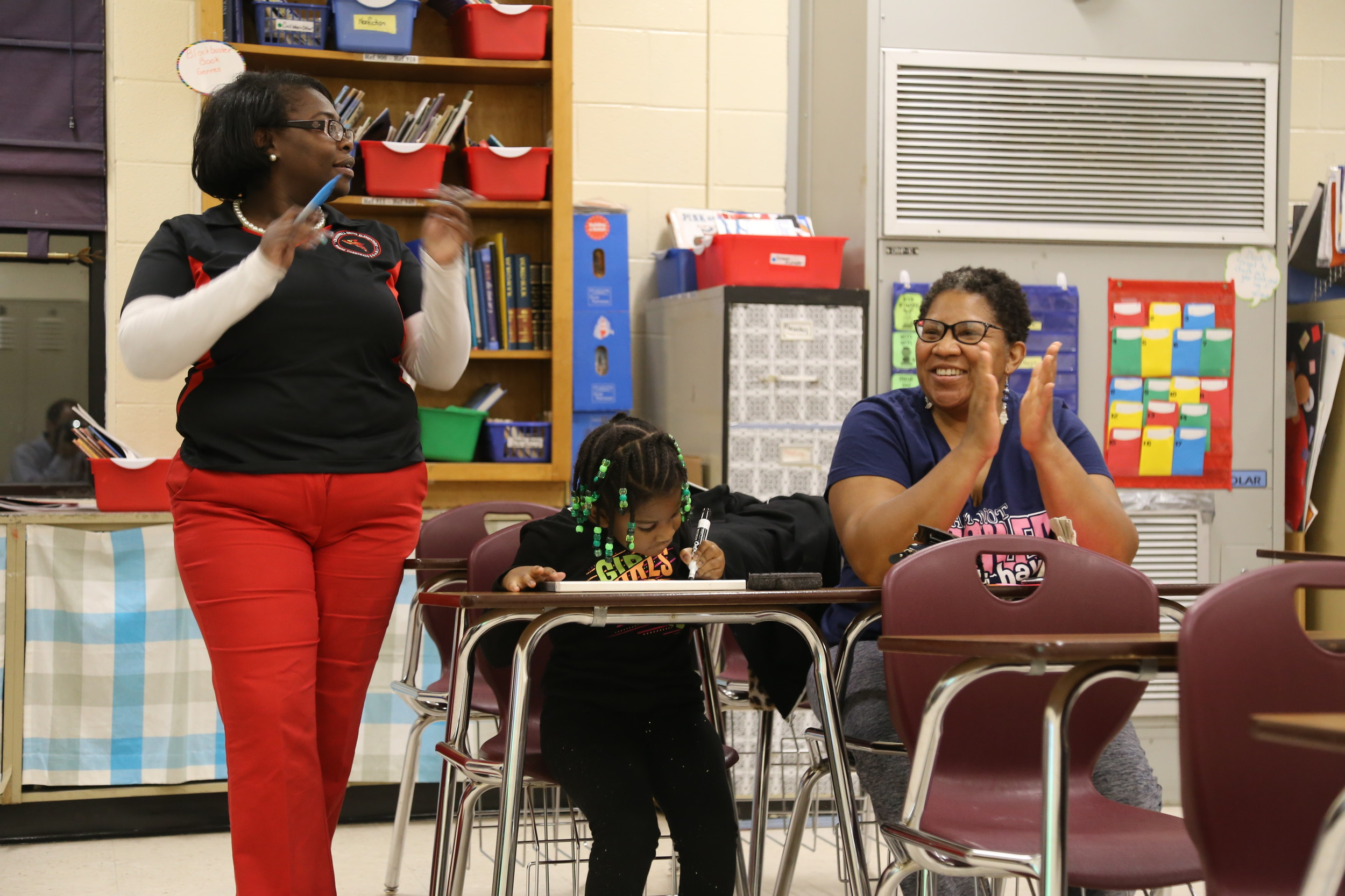 From left, Crosswell Drive Elementary School teacher Fredericka Plowden, student Alena Bradley, and her mother, Dawn Bradley, participate in Family Night at the school.