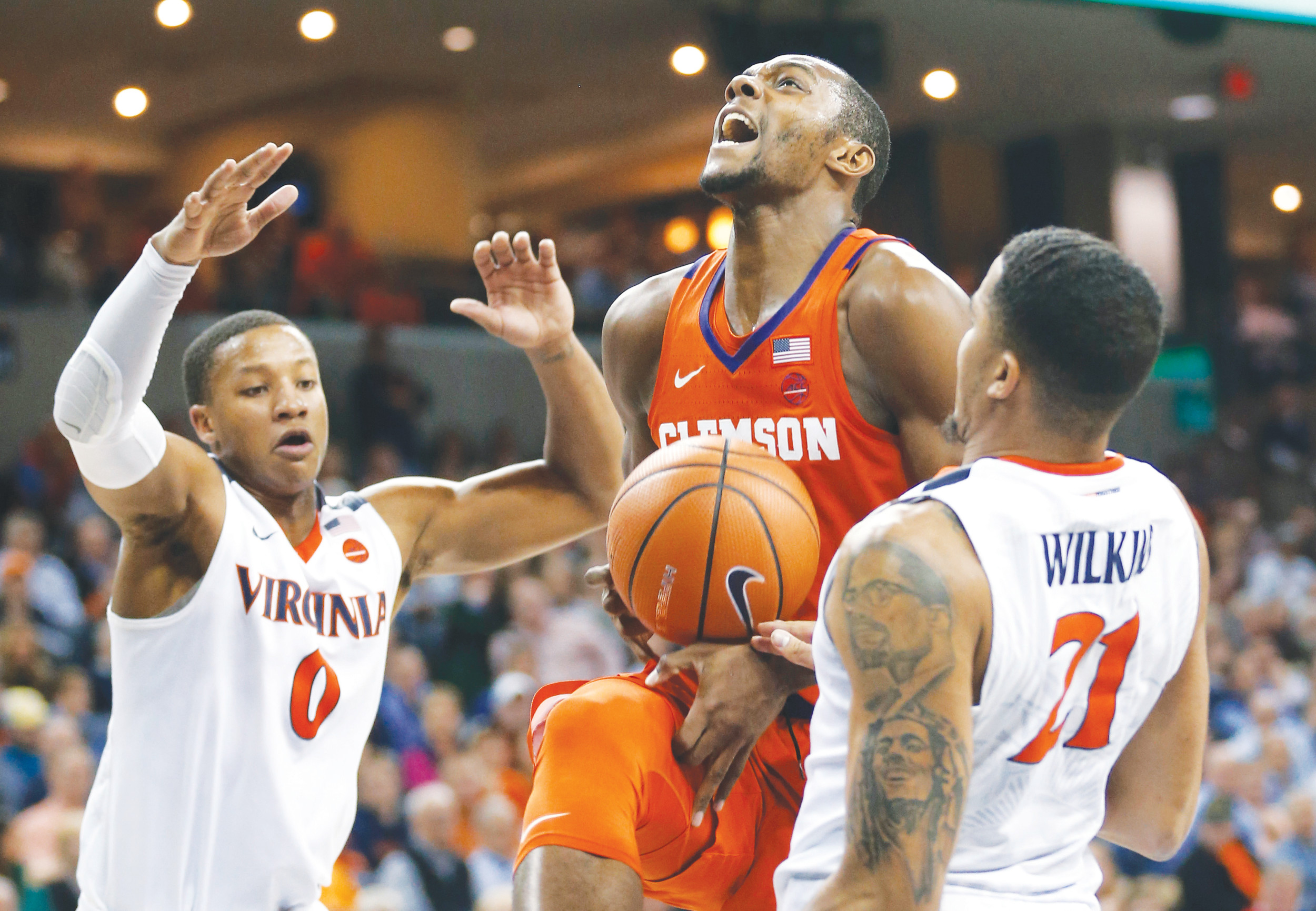 Clemson forward Aamir Simms (25) loses the ball as Virginia guard Devon Hall (0) and forward Isaiah Wilkins (21) defend during the first half of the Cavaliers' 61-36 victory over the Tivers on Tuesday in Charlottesville, Virginia.