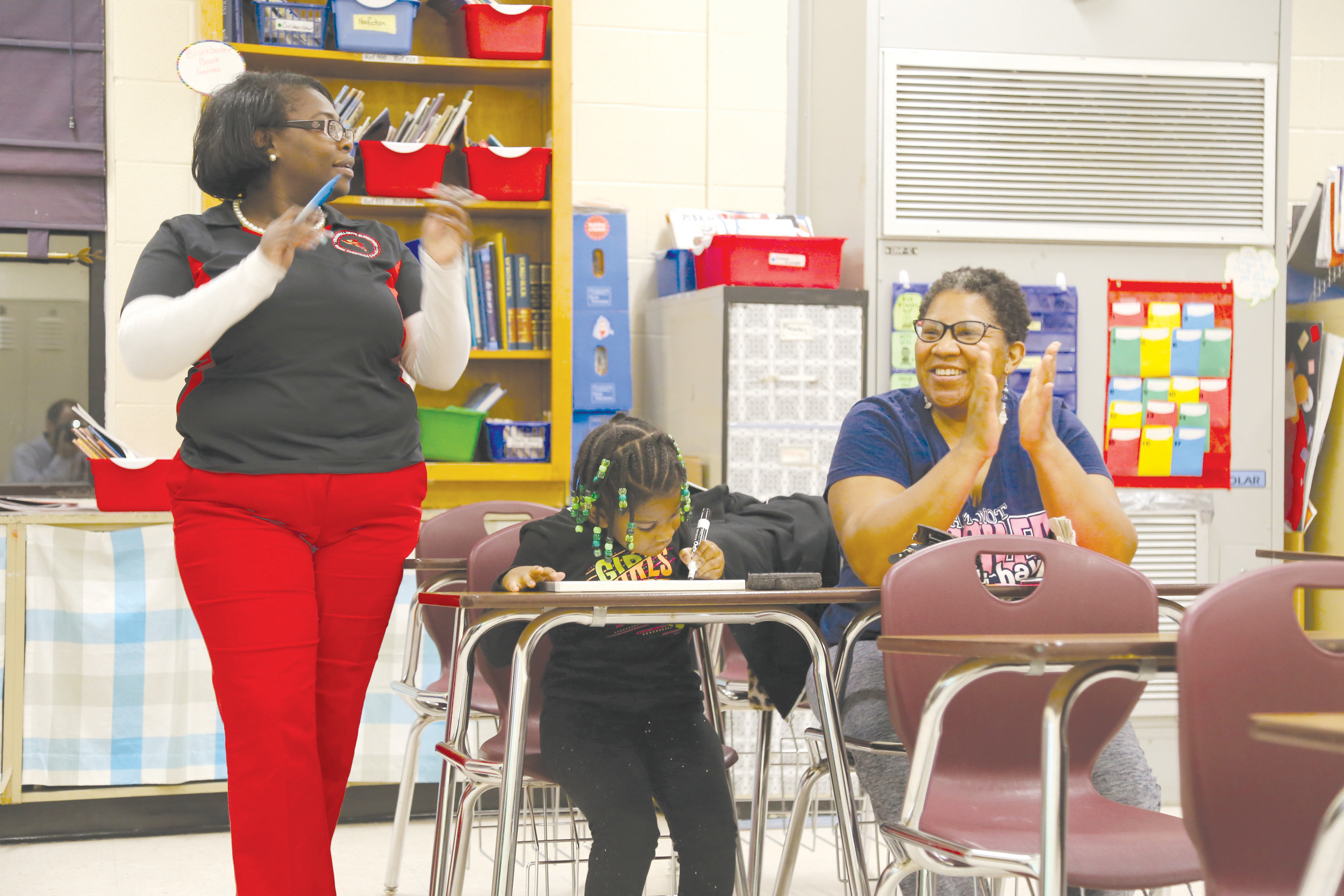 From left, Crosswell Drive Elementary School teacher Fredericka Plowden, student Alena Bradley and her mother, Dawn Bradley, participate in Monday's Family Night at the school.