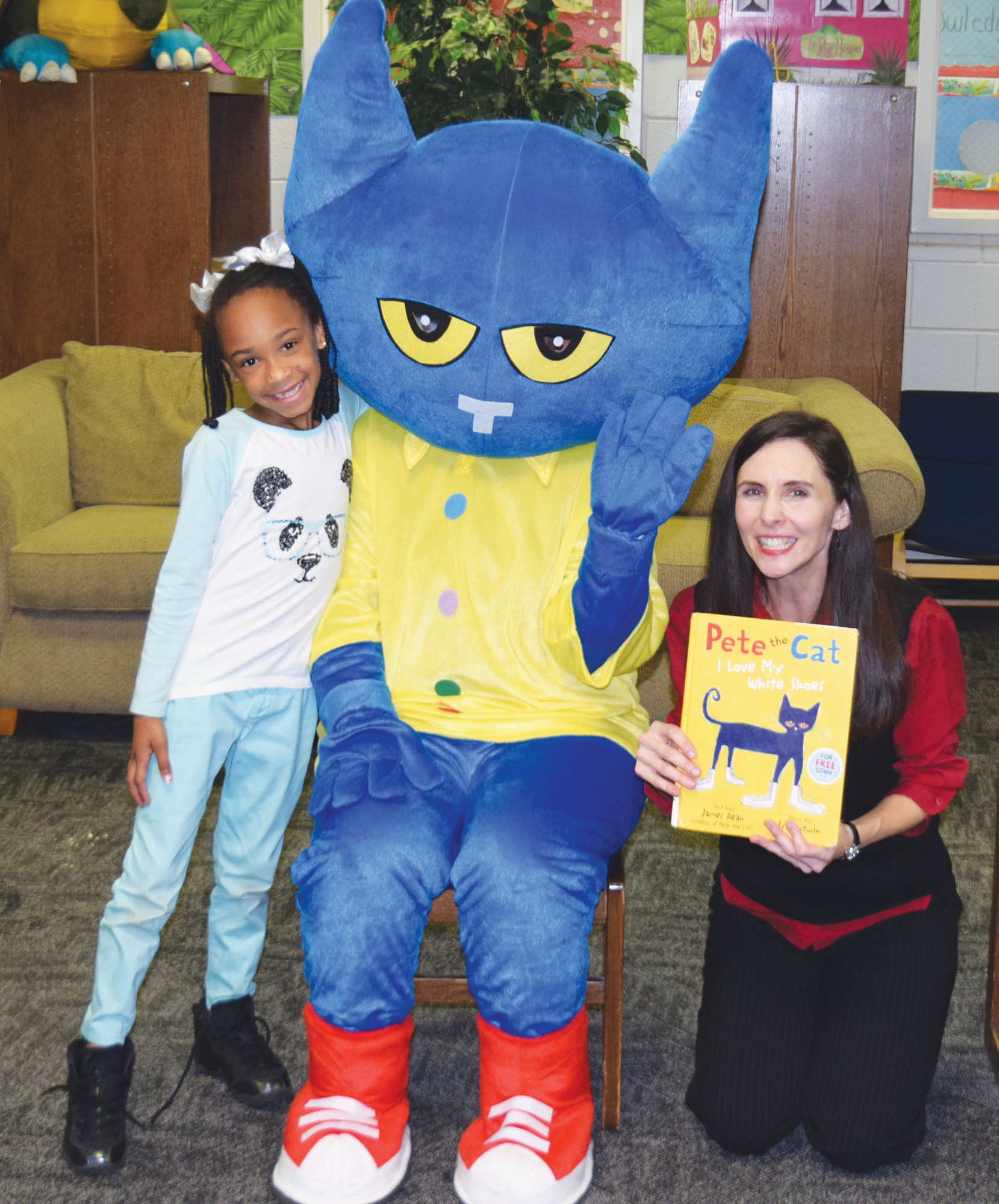 PHOTOS PROVIDEDKingsbury Elementary School first-grader Takiyah Miller meets Pete the Cat at the school's annual Family Reading Night. Holding the book is Christy Smith, director of children's services at the Sumter County Library.