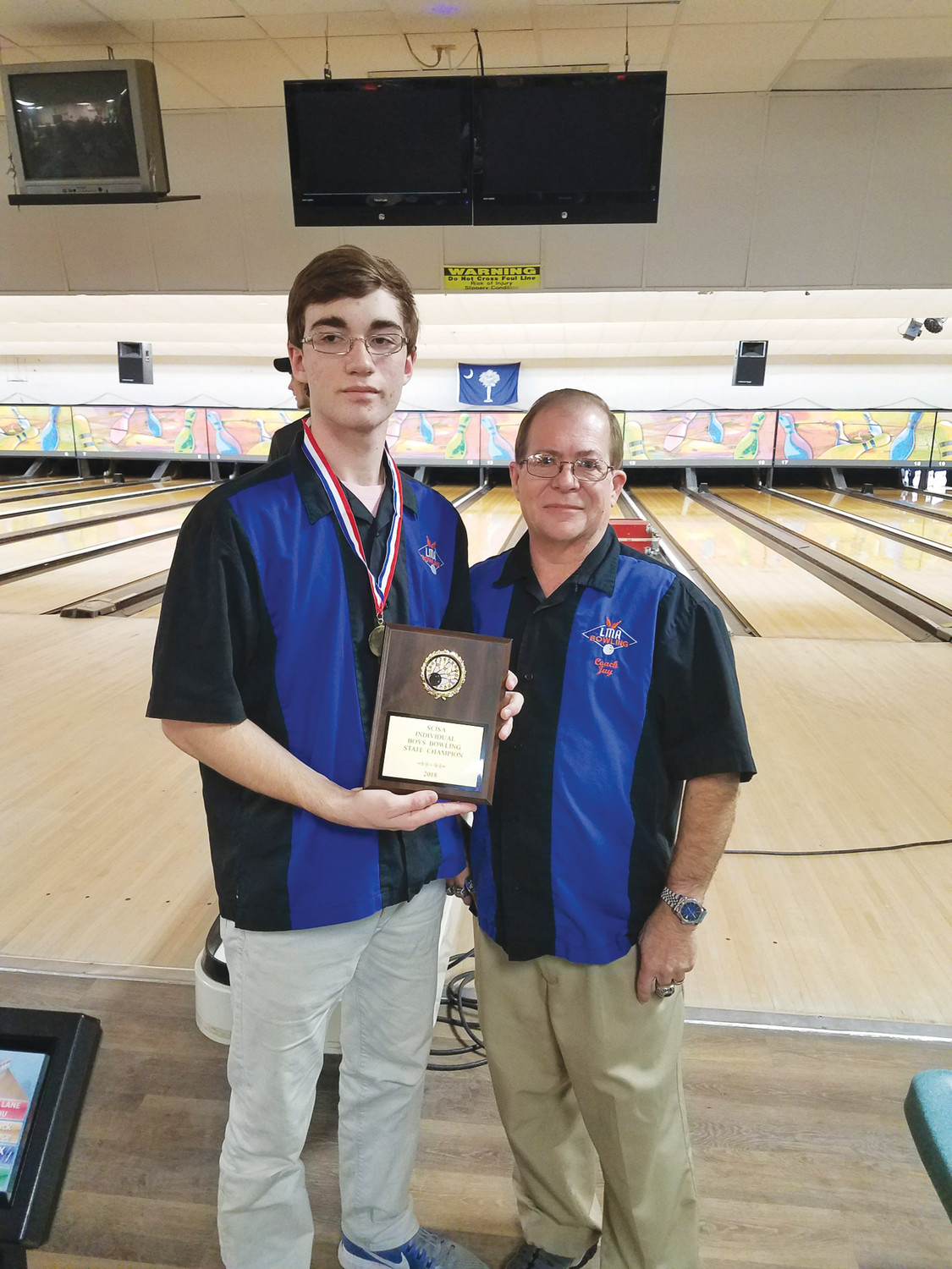 Photo providedLaurence Manning Academy's Mark Lupori, left, shows the plaque he received for winning the SCISA boys individual bowling championship on Thursday at Gamecock Lanes. To his right is LMA head coach Jay Atkins.