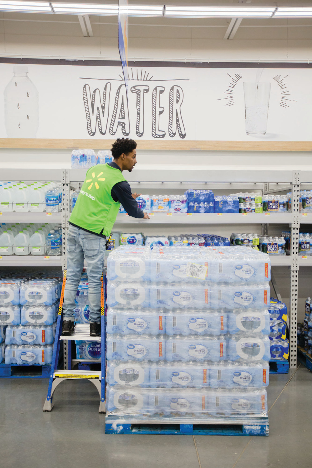 Davion Hawk stocks bottles of water at the new Walmart Neighborhood Market ahead of its grand opening this morning.