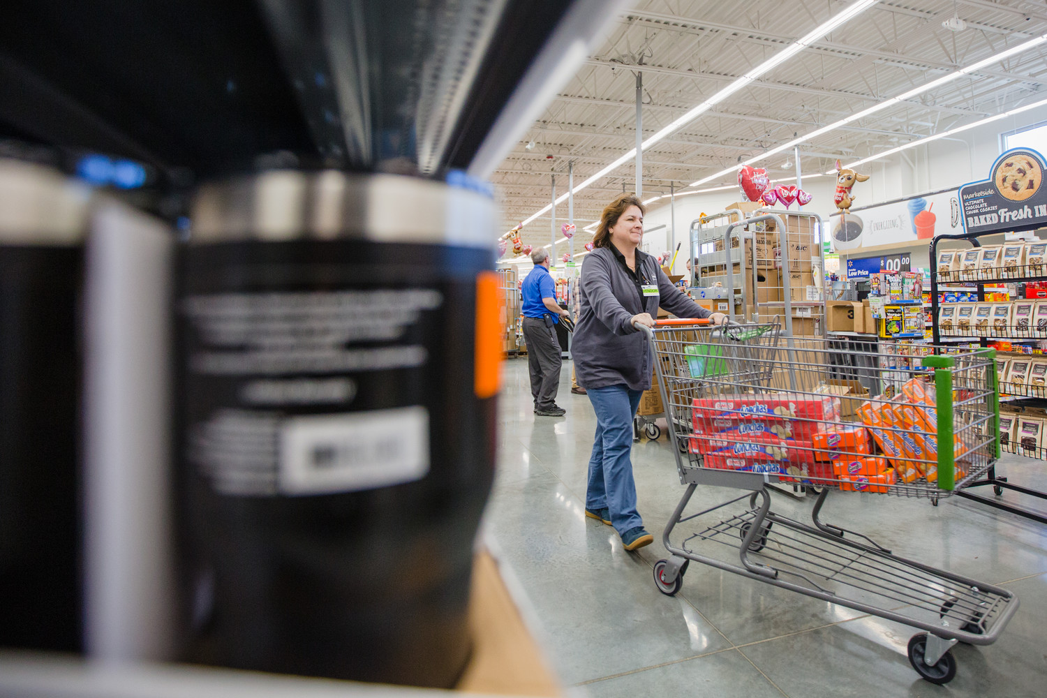 An employee takes products to their shelf homes on Tuesday at the new Walmart Neighborhood Market.