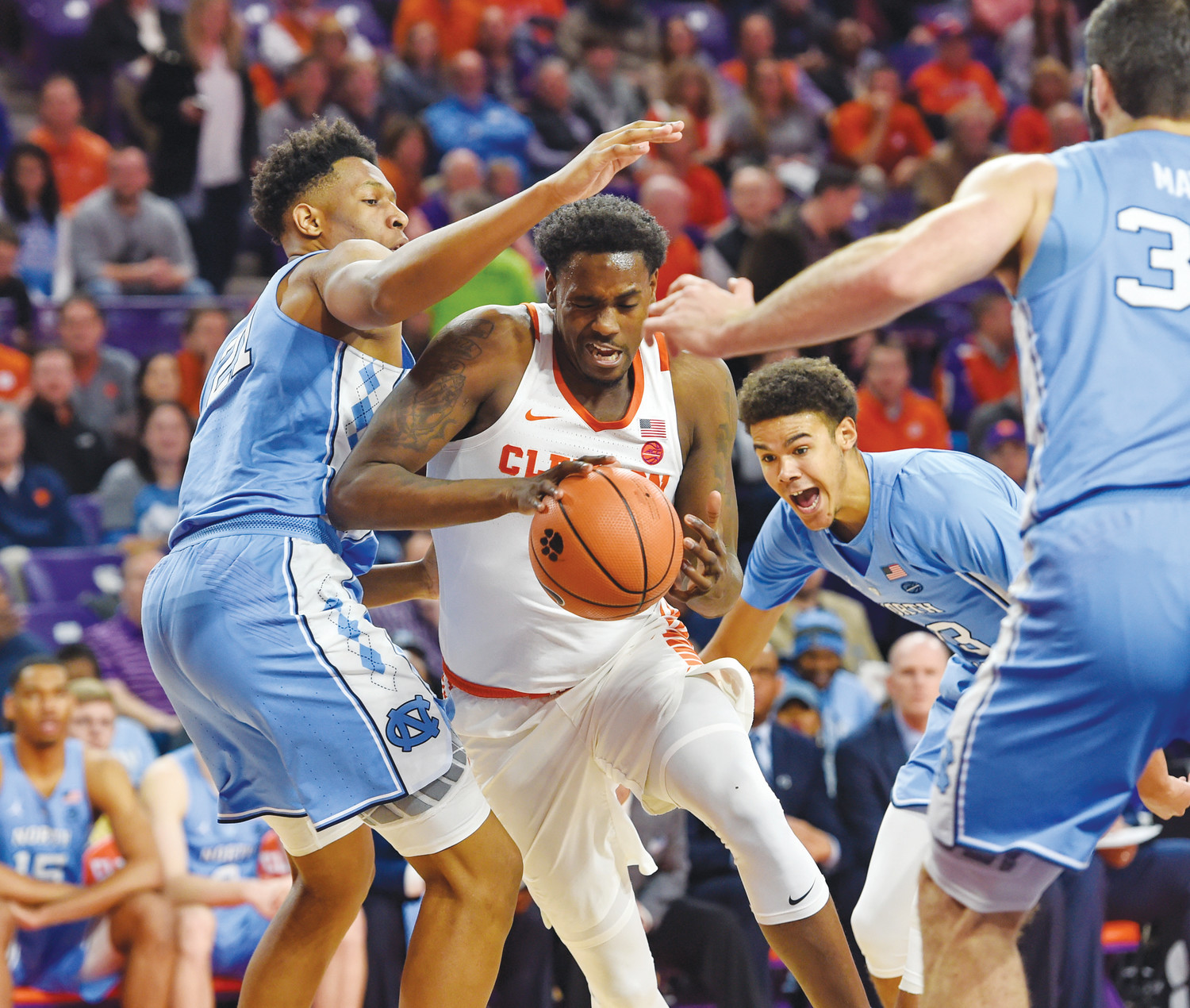 Clemson's Elijah Thomas, center, drives between North Carolina defenders, including Sterling Manley, left, during the first half of their game Tuesday in Clemson.
