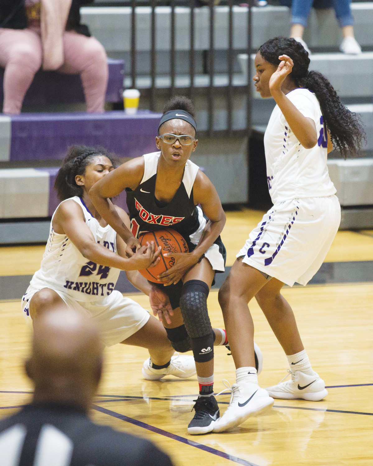 Crestwood's Brittany Epps and Sedajah Remert fight for a ball with a Hartsville player during the Lady Knights' 65-63 loss to the Red Foxes on Tuesday at The Castle.