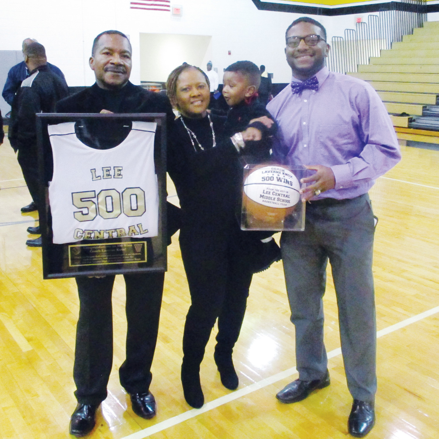 Lee Central High School varsity boys basketball head coach LaVerne Knox, left, holds a framed jersey commemorating his 500th win, a 81-45 pasting of Central on Tuesday at the LCHS gymnasium. Knox is seen at the ceremony at the school celebrating the victory with his wife, Joann, middle, son, Brad, right and a grandson, Braylen, 2. This story has been edited for length. Read the full story at at www.theitem.com.
