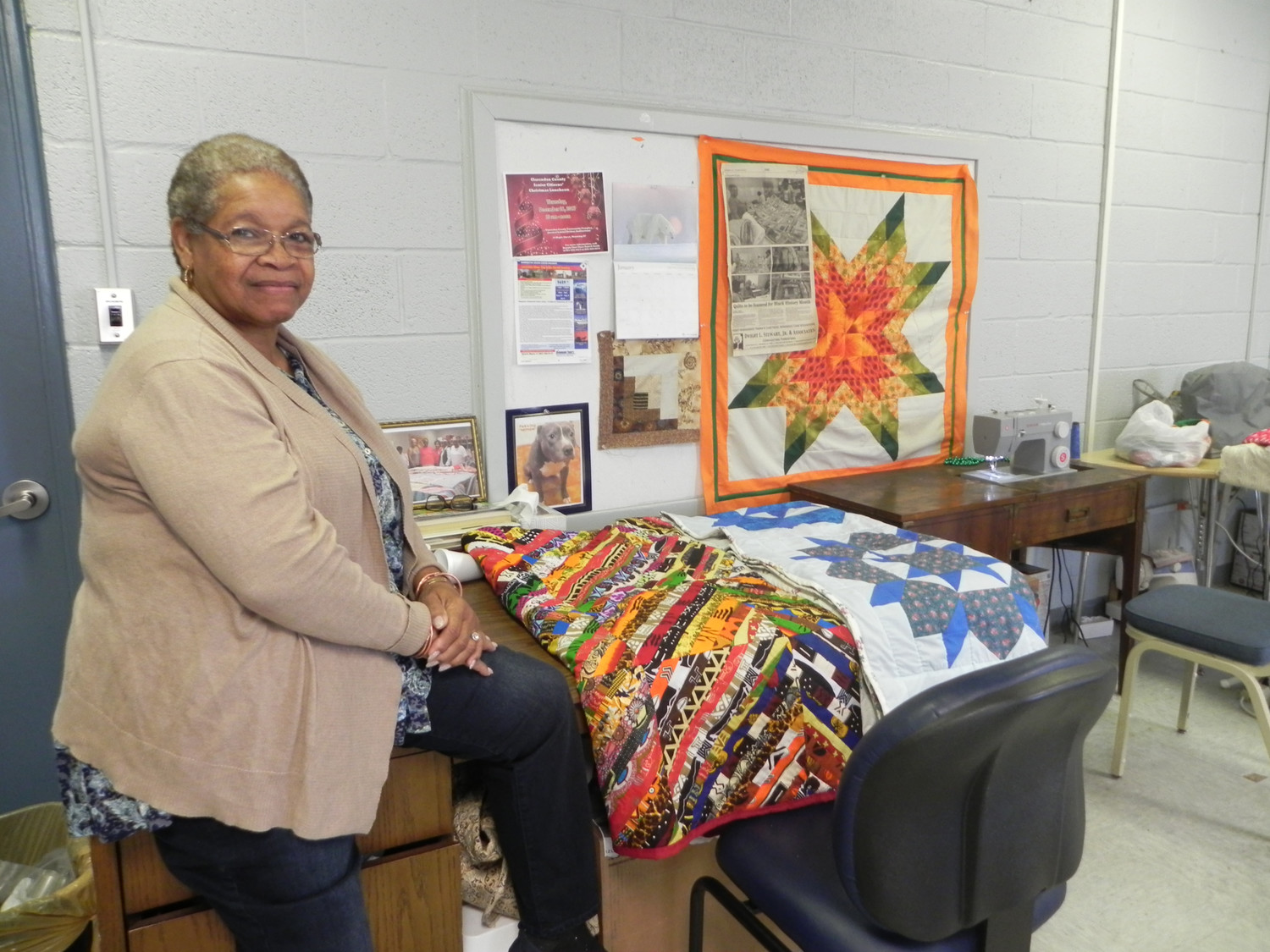 Geneva Bell, from the Summerton Senior Quilters, proudly displays a few of the quilts her group made for the show she helped coordinate at the Lake Marion Artisans Art Gallery.