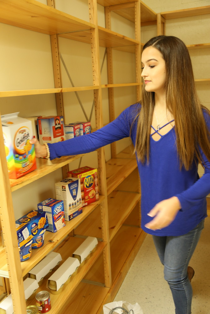 ADRIENNE SARVIS / THE SUMTER ITEMHannah Young, 2018 Miss Georgetown County Teen, places food on the shelf of a pantry in preparation for the launch of Backpack Buddies, her program to feed food-insecure elementary school students.