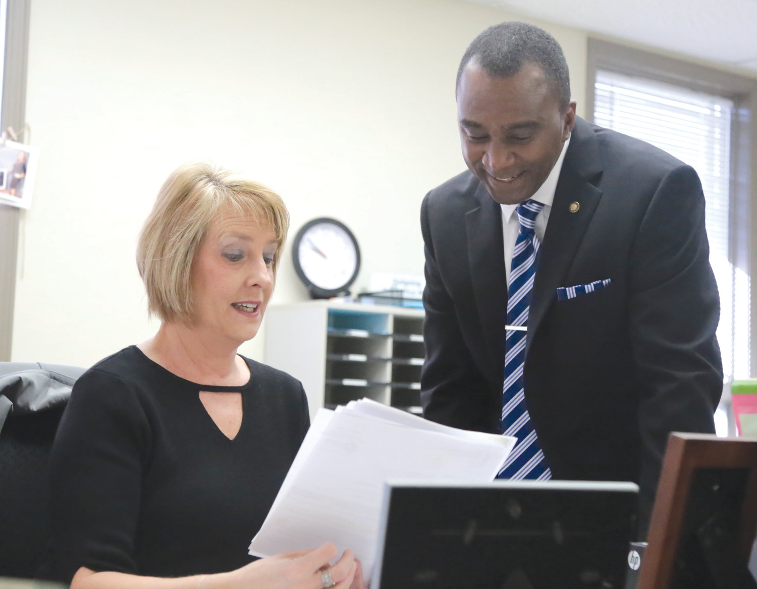 New Santee-Lynches Regional Council of Governments Executive Director Chris McKinney, right, goes through materials with Administrative Assistant Becky Minegar on Tuesday at the COG's headquarters, 2525 Corporate Way.