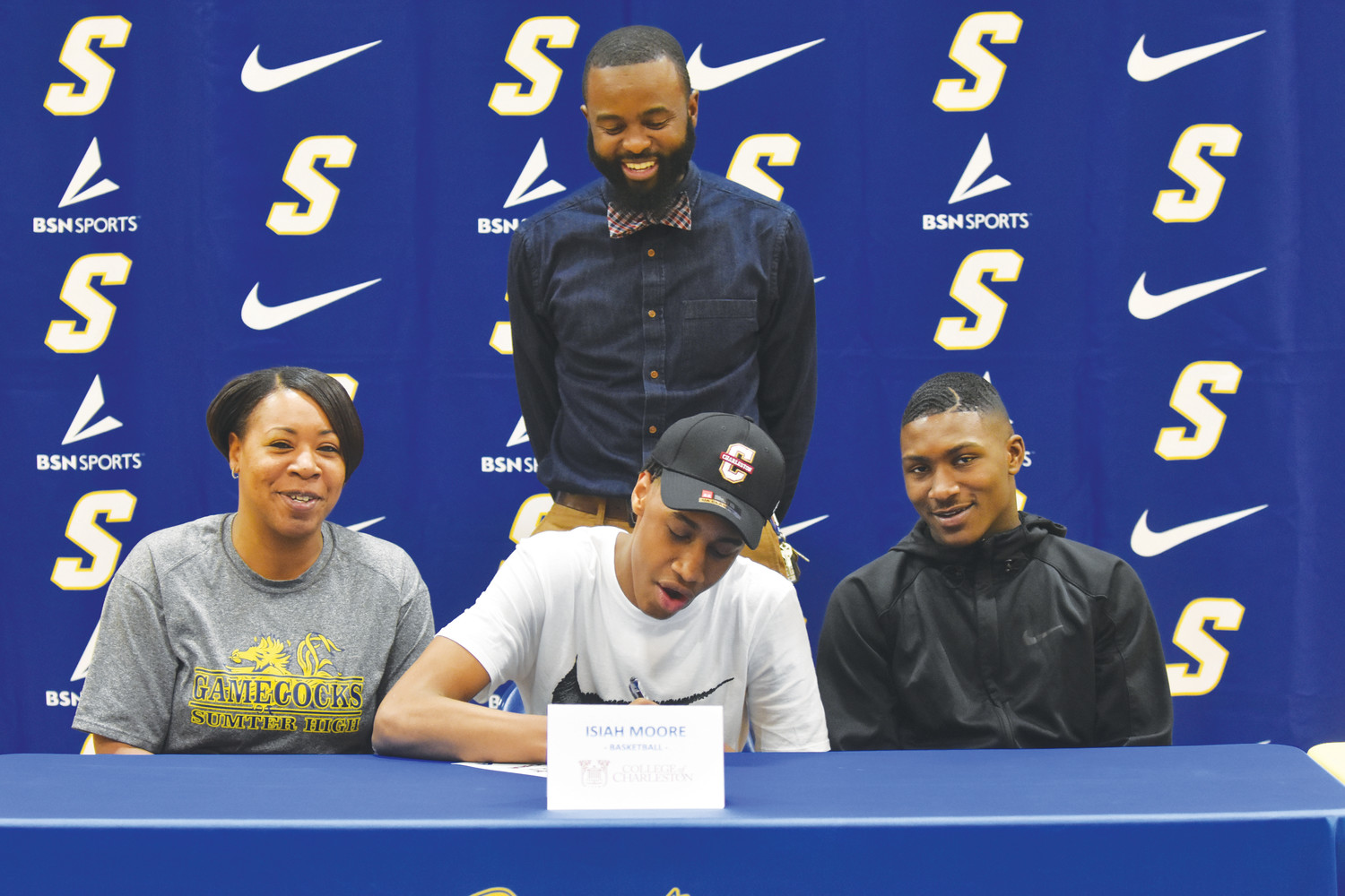 Sumter High School's Isaih Moore, is seen sporting a College of Charleston cap for National Signing Day on Wednesday. The 6-10 forward, flanked by his mother, Shannon Jones (left), his brother Isiah Pinckney and SHS assistant coach Reynard Jefferson, as he announces his signing.