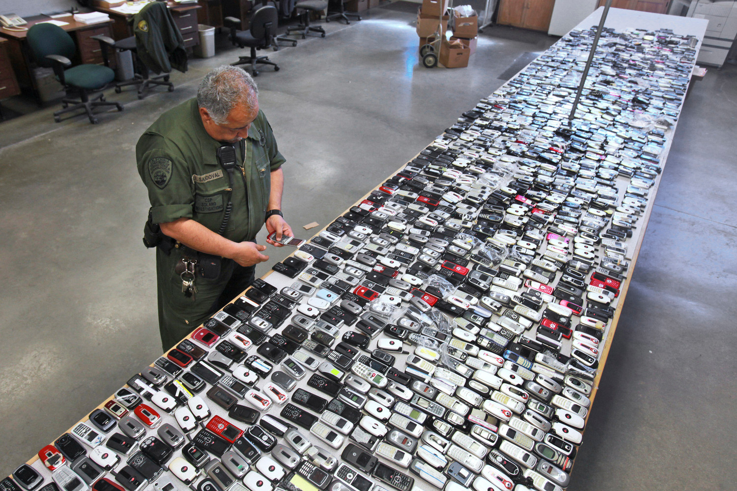 AP FILE PHOTOCorrectional Officer Jose Sandoval inspects one of the more than 2,000 cell phones confiscated from inmates at California State Prison, Solano in Vacaville, California.
