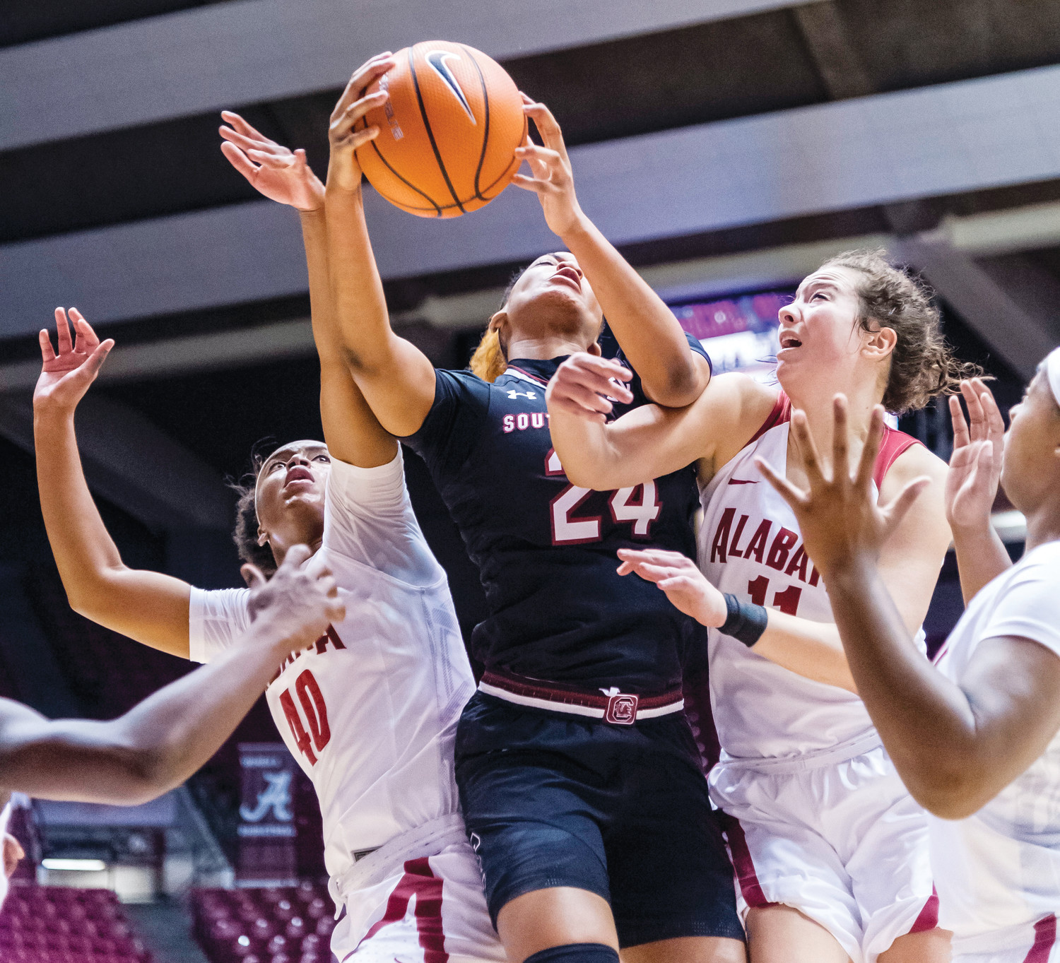 South Carolina forward LeLe Grissett (24) fights for possession under the basket against Alabama forward Jasmine Walker (40) and guard Hannah Cook (11) during the Gamecocks' 79-66 victory over the Crimson Tide on  Thursday in Tuscaloosa, Alabama.