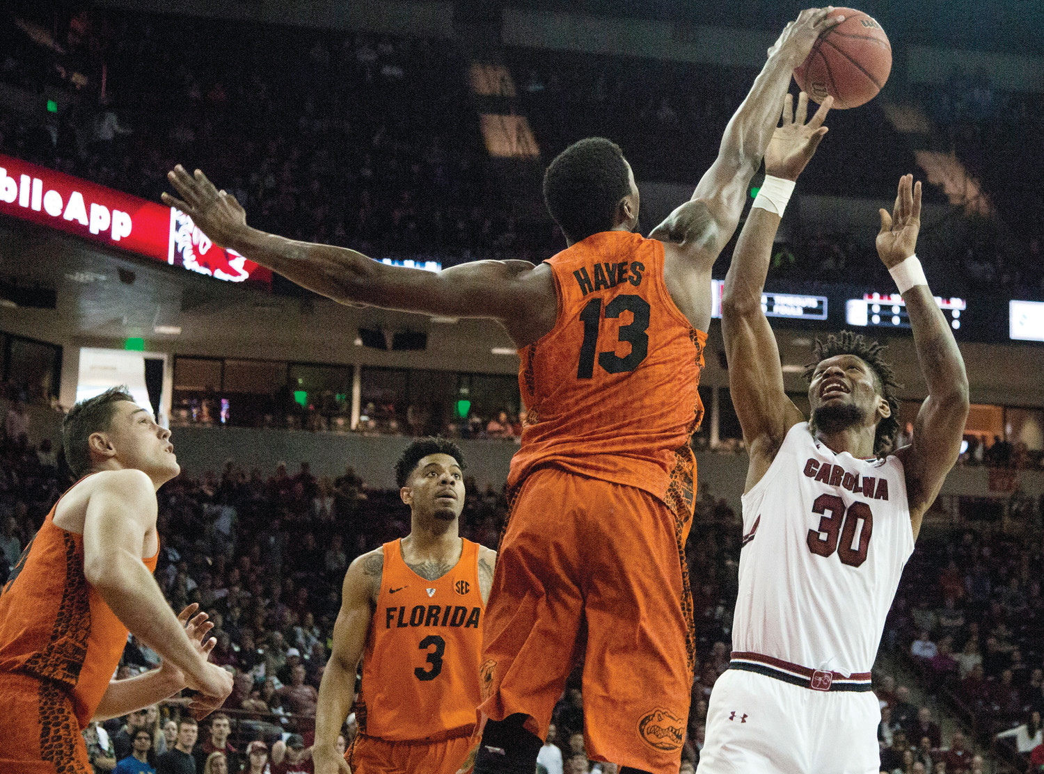 THE ASSOCIATED PRESS  Florida forward Kevarrius Hayes (13) blocks the shot of South Carolina forward Chris Silva (30) during the first half of Florida's 65-41 dismantling of the Gamecocks in Columbia on Saturday.