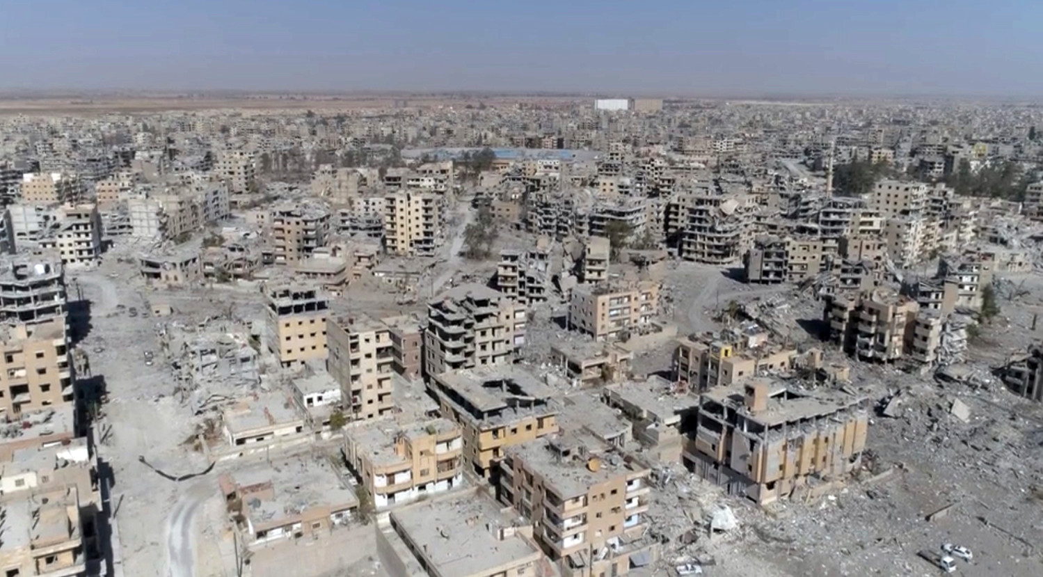 "An image from drone video shows damaged buildings in Raqqa, Syria, two days after Syrian Democratic Forces said military operations to oust the Islamic State group ended. A U.S. military official says that the American-backed Syrian Democratic Forces in January 2018 captured two notorious British members of an Islamic State insurgent cell commonly dubbed ""The Beatles"" and known for beheading hostages."