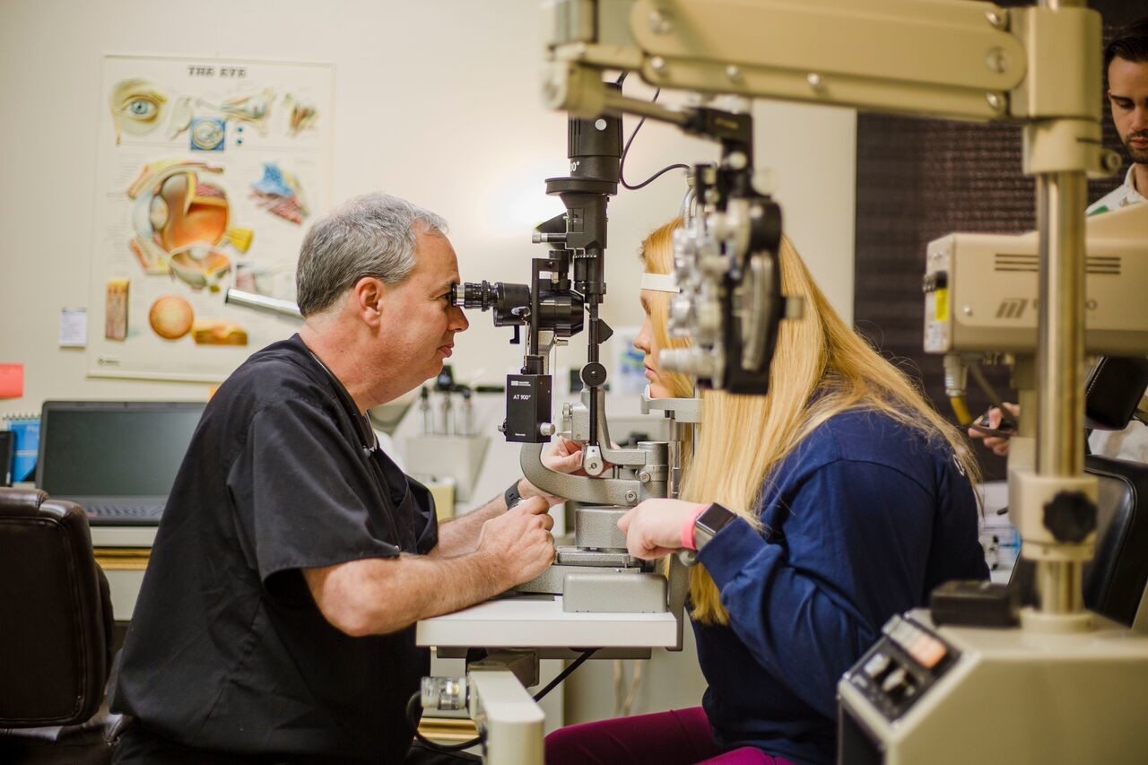 Dr. Howard Greene, left, uses a binocular microscope to examine a patient's eye for inflammation Friday at Eye Care Specialty Center, 528 Broad St. Greene is one of three eye surgeons in the state who performs a new procedure called Kamra Inlay.