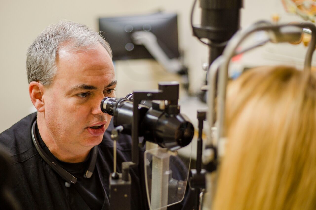 Dr. Howard Greene uses a binocular microscope to examine a patient's eye for inflammation Friday at Eye Care Specialty Center, 528 Broad St. Greene is one of three eye surgeons in the state who performs a new procedure called Kamra Inlay.