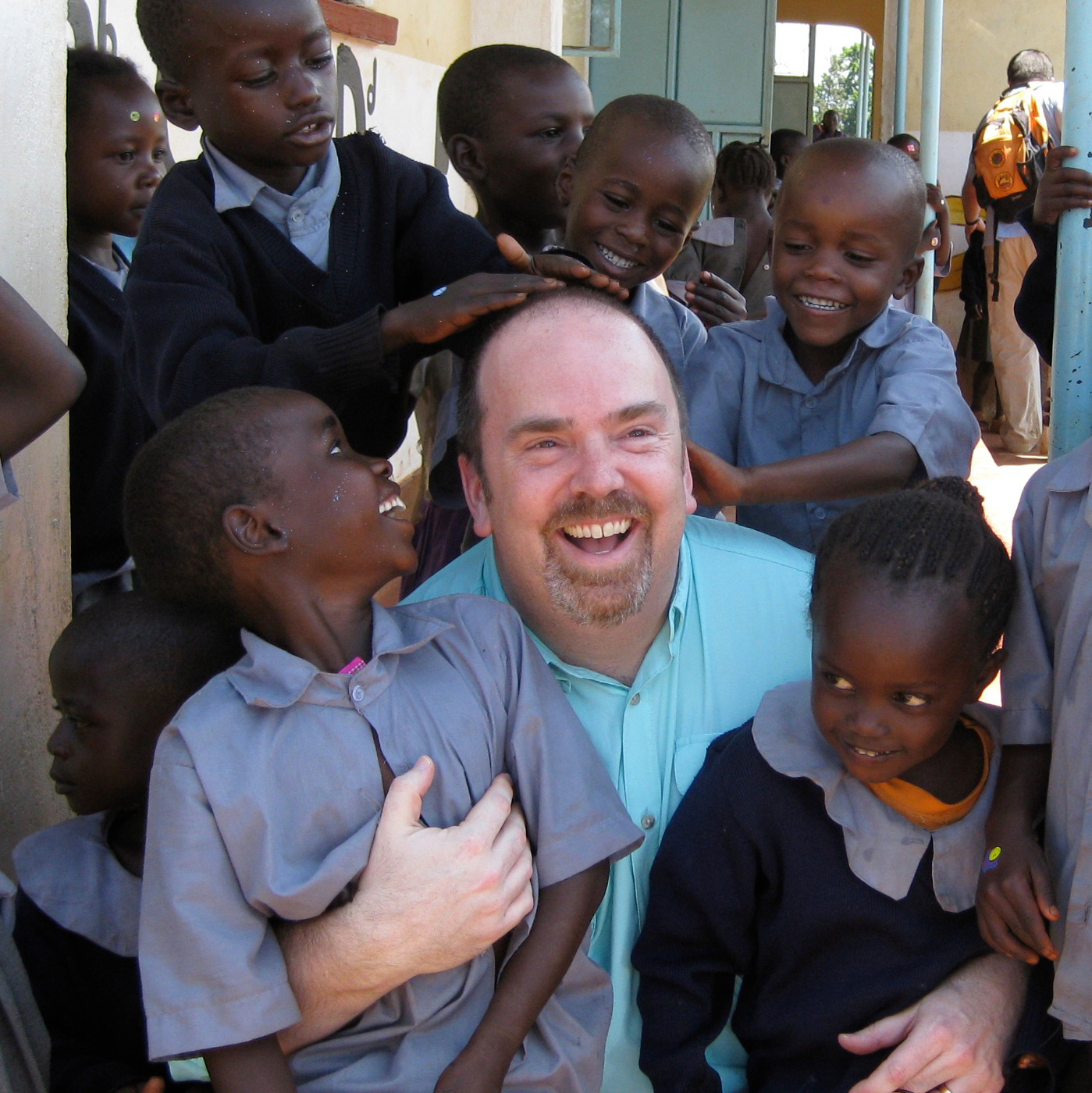 This photo, taken in Nairobi, Kenya, shows Greg Eubanks, CEO of an adoption agency in Washington state called WACAP, surrounded by students from a community elementary school. Eubanks says his agency, and other U.S. adoption agencies dealing in international adoption, face difficulties ahead because of higher fees and tougher regulations being imposed by the U.S. State Department.