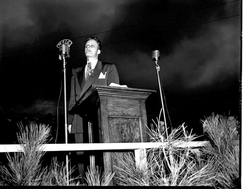 The Rev. Billy Graham is shown on the stage set up for him to deliver his sermon to a packed football stadium on the Sumter fairgrounds in 1950. Note the microphones: Those who couldn't go to the service could listen at home on the radio, as WFIG broadcast it live.