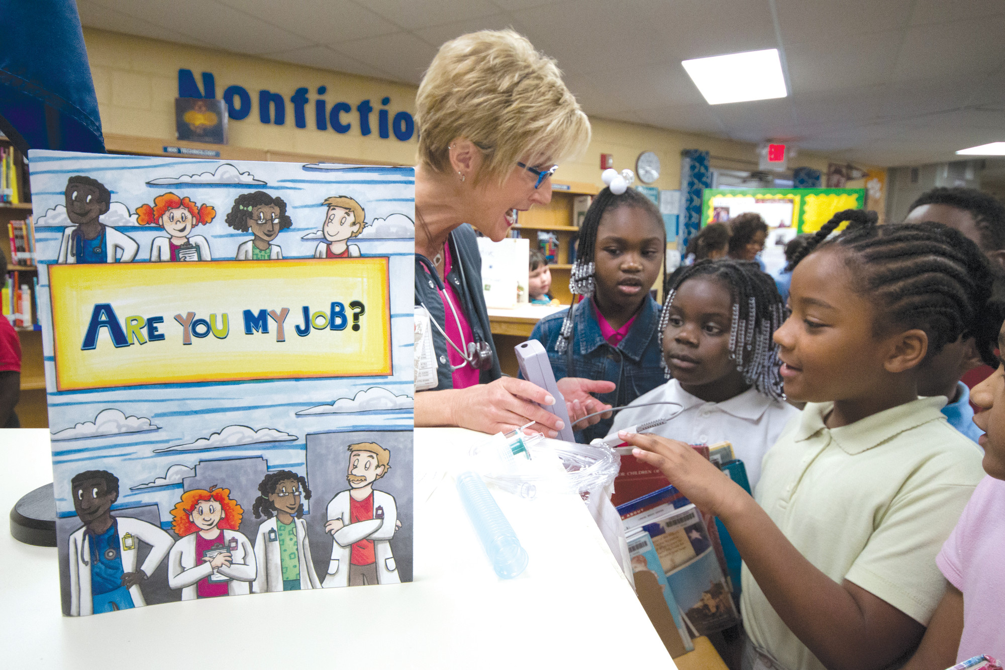 CHRIS MOORE / PALMETTO HEALTH TUOMEYSonya McDaniel, left, clinical respiratory care manager at Palmetto Health Tuomey, teaches second graders at Lemira Elementary School on Thursday about her job. The hospital unveiled the book, Are You My Job?, detailing hospital careers at the school.