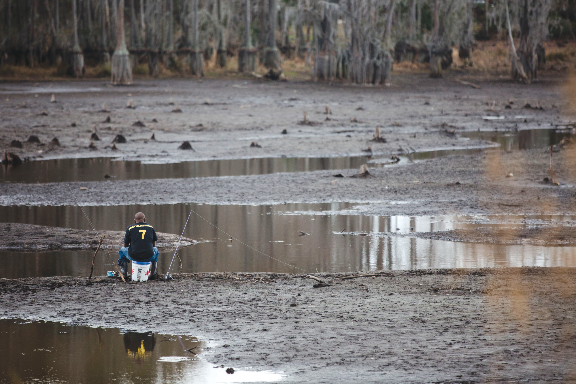 A man fishes in the low water of Second Mill Pond recently. After two years of working with the Federal Emergency Management Agency and contractors for the project, repair work on the dam started in late January. It was damaged after the flood in 2015.