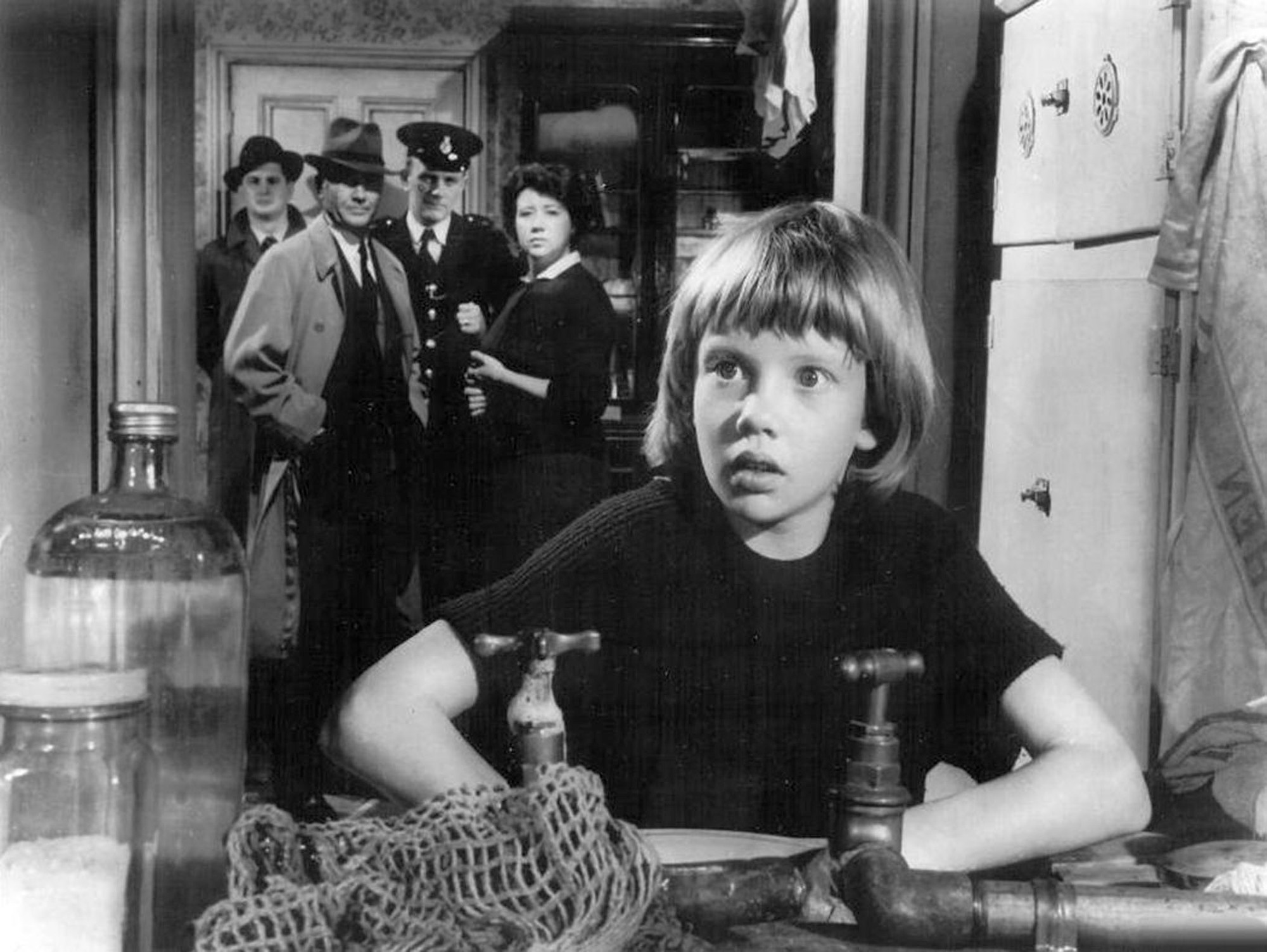 "Hayley Mills with father John Mills in the background as a police inspector in ""Tiger Bay"" - The Rank Organisation"