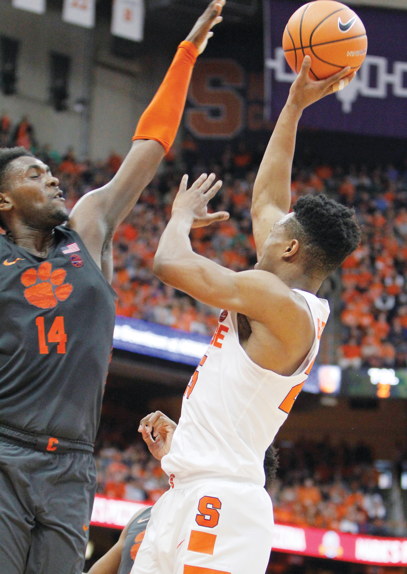 Clemson's Elijah Thomas, left, blocks a shot from Syracuse's Tyus Battle, right during the second half of Syracuse's win over Clemson in the regular season finale for both teams Friday in Syracuse, New York.