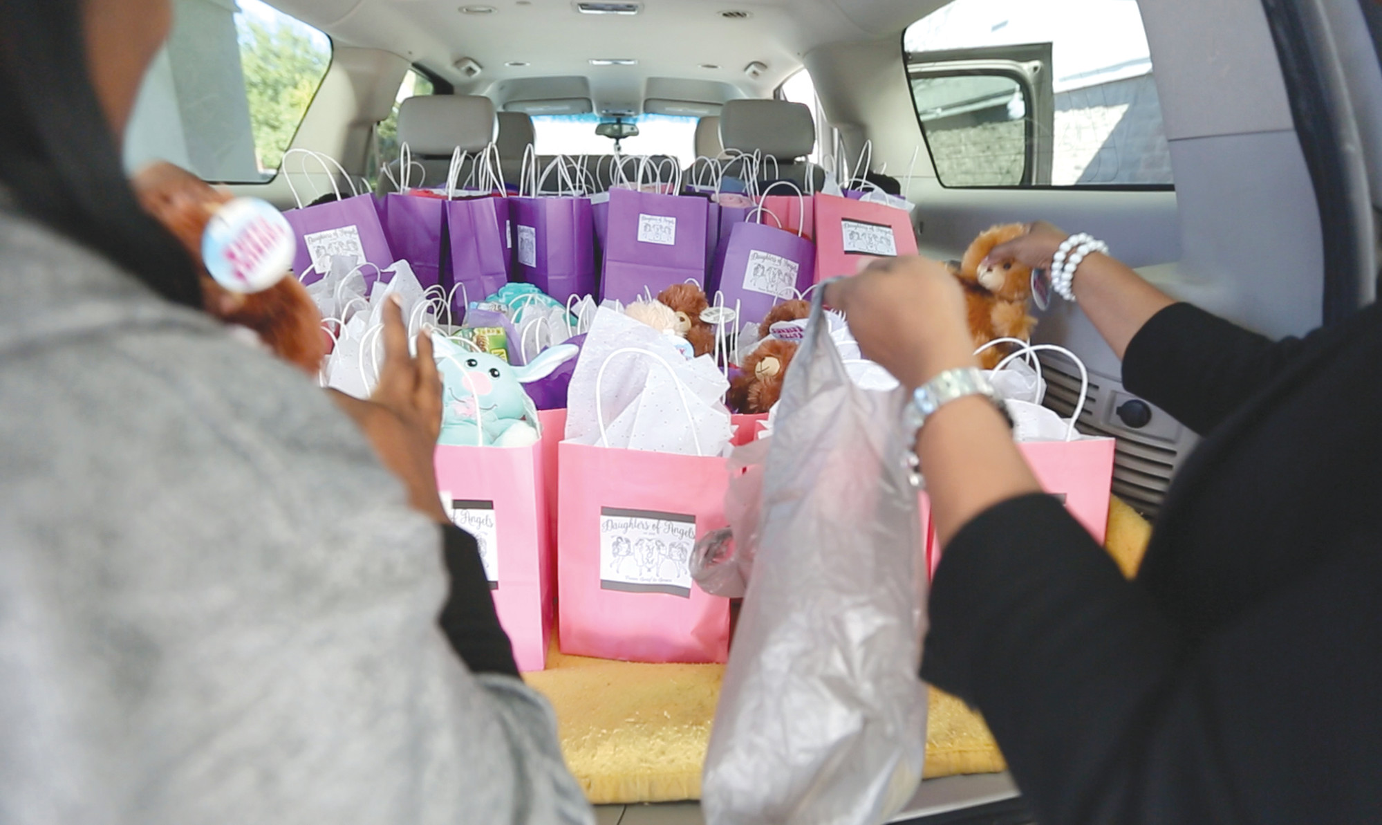 Members of Daughters of Angels pack gift bags before delivering them to Santee Hematology Oncology on Friday.