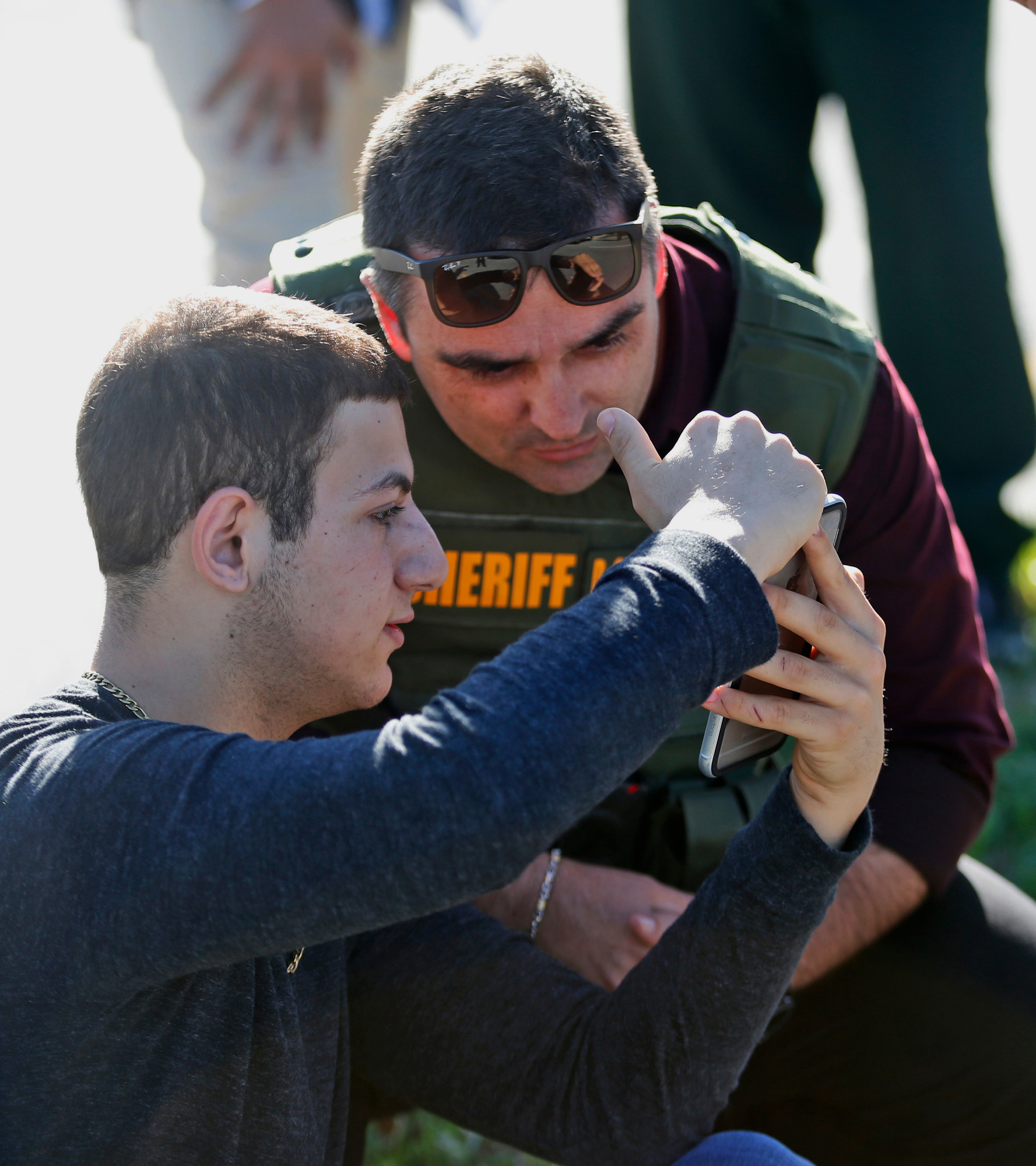 A Marjory Stoneman Douglas High School student shows a law enforcement officer a video from his phone in Parkland, Florida. Modern technology has enabled real-time reaction, support and calls for action during deadly mass shootings in the U.S.
