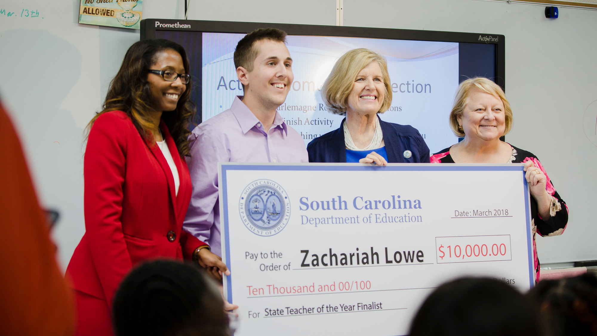 Zachariah Lowe holds a check for $10,000 along with State Superintendent Molly Spearman, right, after being surprised at Mayewood Middle School.
