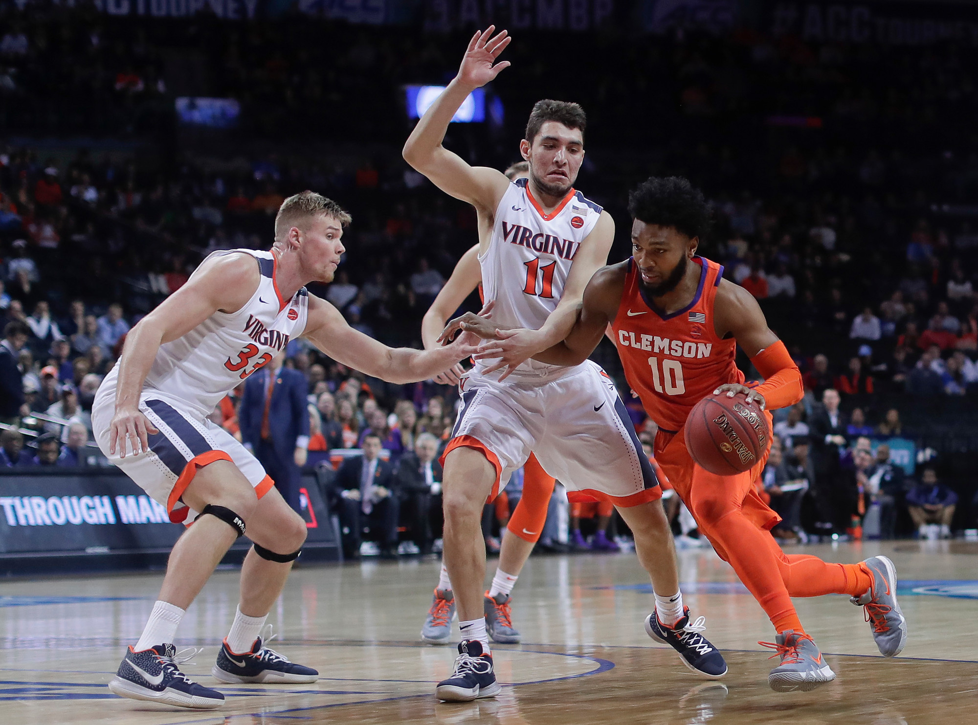 Clemson guard Gabe DeVoe (10) drives against Virginia center Jack Salt (33) and guard Ty Jerome (11) during the Tigers' 64-58 loss in an Atlantic Coast Conference tournament semifinal game on Friday in New York.