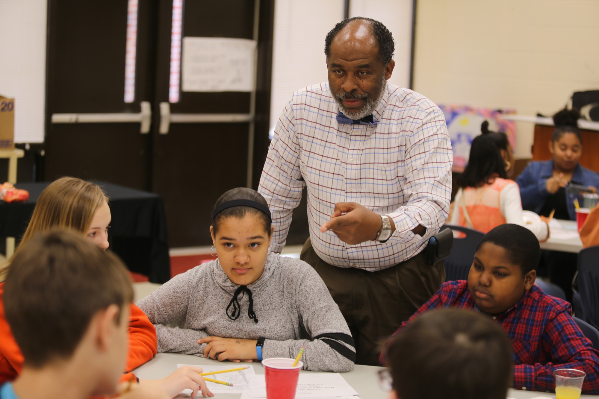 Adult volunteer Chuck Wilson leads a discussion at his table with Bates Middle School students during an intergenerational program session at the school on Wednesday.