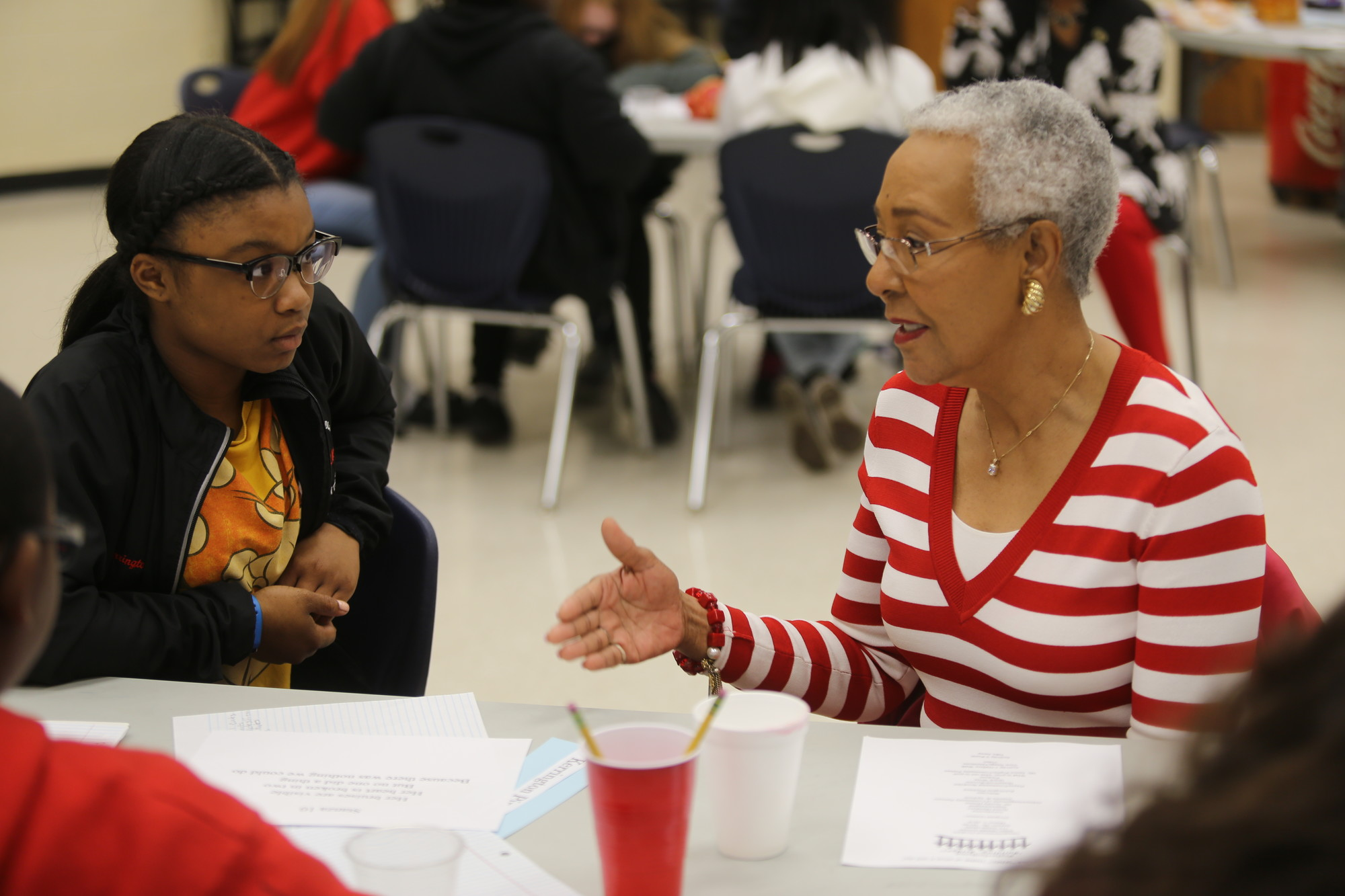 Bates Middle School student Kerrington Pinckney listens Wednesday as adult volunteer Gloria Summers talks Wednesday during an intergenerational program session at the school.