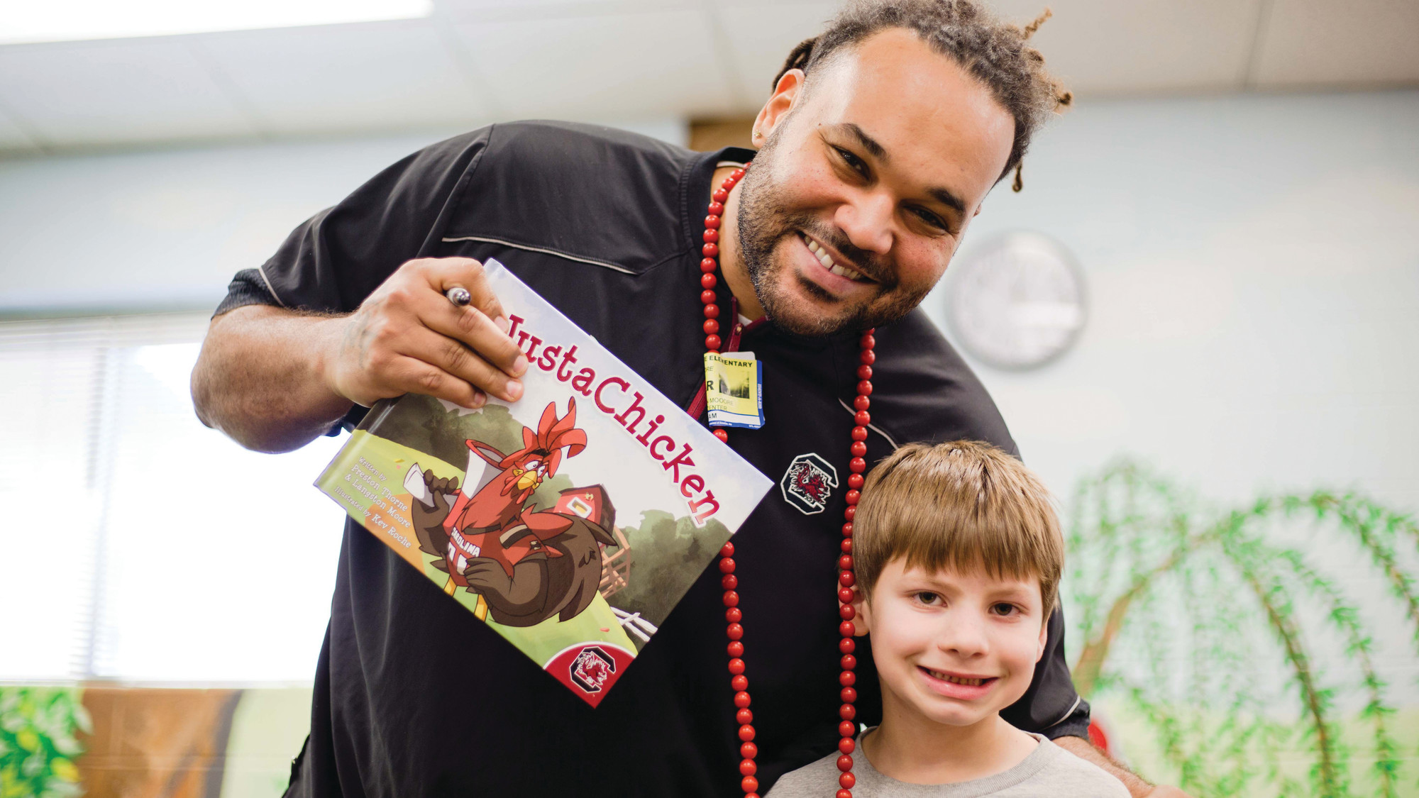 Former Gamecock football player Langston Moore poses for a picture with a Willow Drive Elementary School student Friday with his book #JustaChicken. He wrote the motivational book with former USC teammate Preston Thorne.