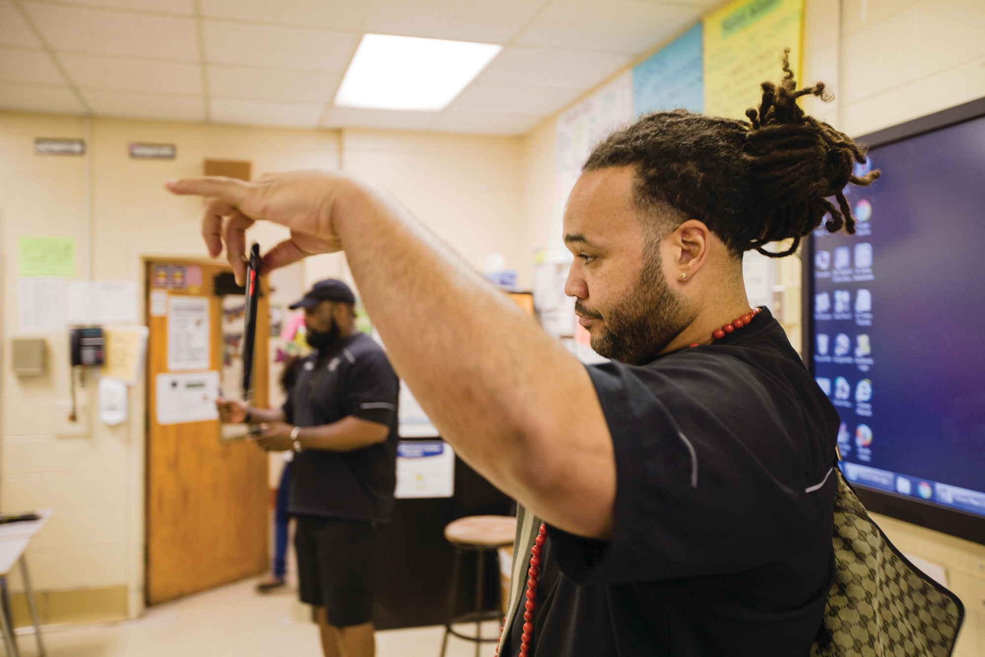 Former Gamecock football standout Langston Moore shows students his cellphone Friday during a visit to Willow Drive Elementary School. He told students since cellphones are a reading device and so handy these days, there's never an excuse for them not to read.