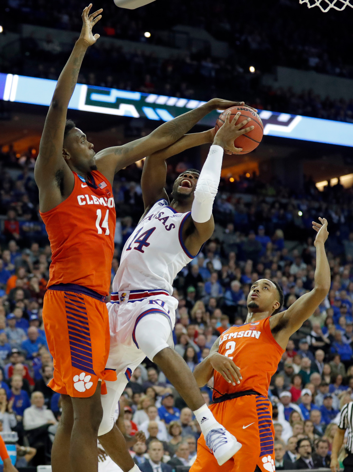 Clemson's Elijah Thomas (14) blocks the shot of Kansas' Malik Newman during the Tigers' 80-76 loss of a Midwest regional semifinal game in the NCAA tournament on Friday in Omaha, Nebraska.
