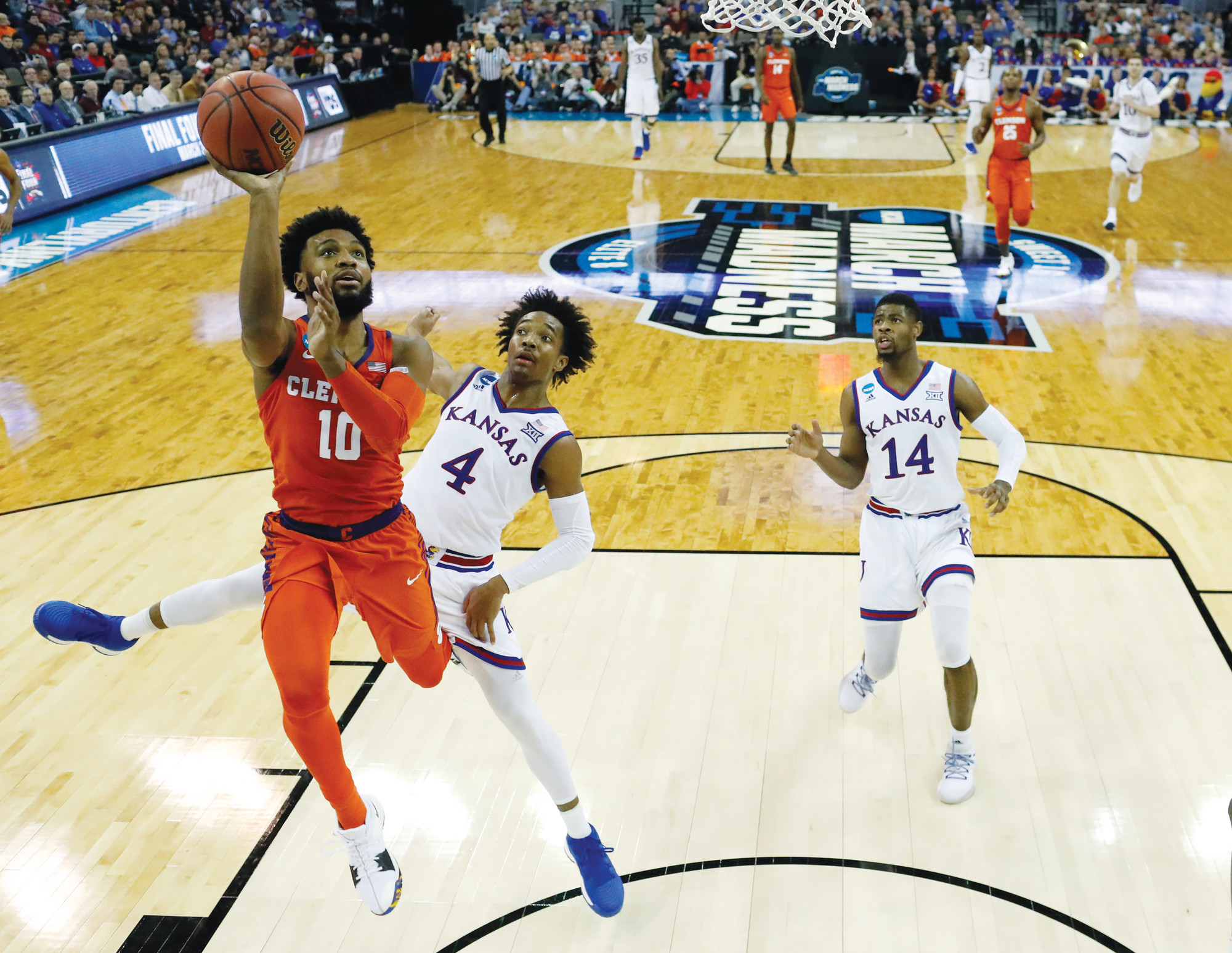 Clemson's Gabe DeVoe (10) heads to the basket as Kansas' Devonte' Graham (4) and Malik Newman defend during the second half of the Tigers' 80-76 loss to the Jayhawks in their regional semifinal game in the NCAA  tournament on Friday in Omaha, Nebraska.