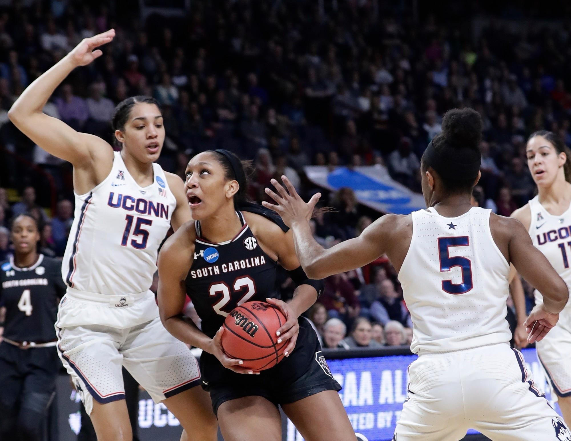 South Carolina's A'ja Wilson (22) drives past Connecticut's Gabby Williams (15) and Crystal Dangerfield (5) during the Gamecocks' 94-65 loss in the Albany Regional championship game of the women's NCAA tournament on Monday in Albany, N.Y.