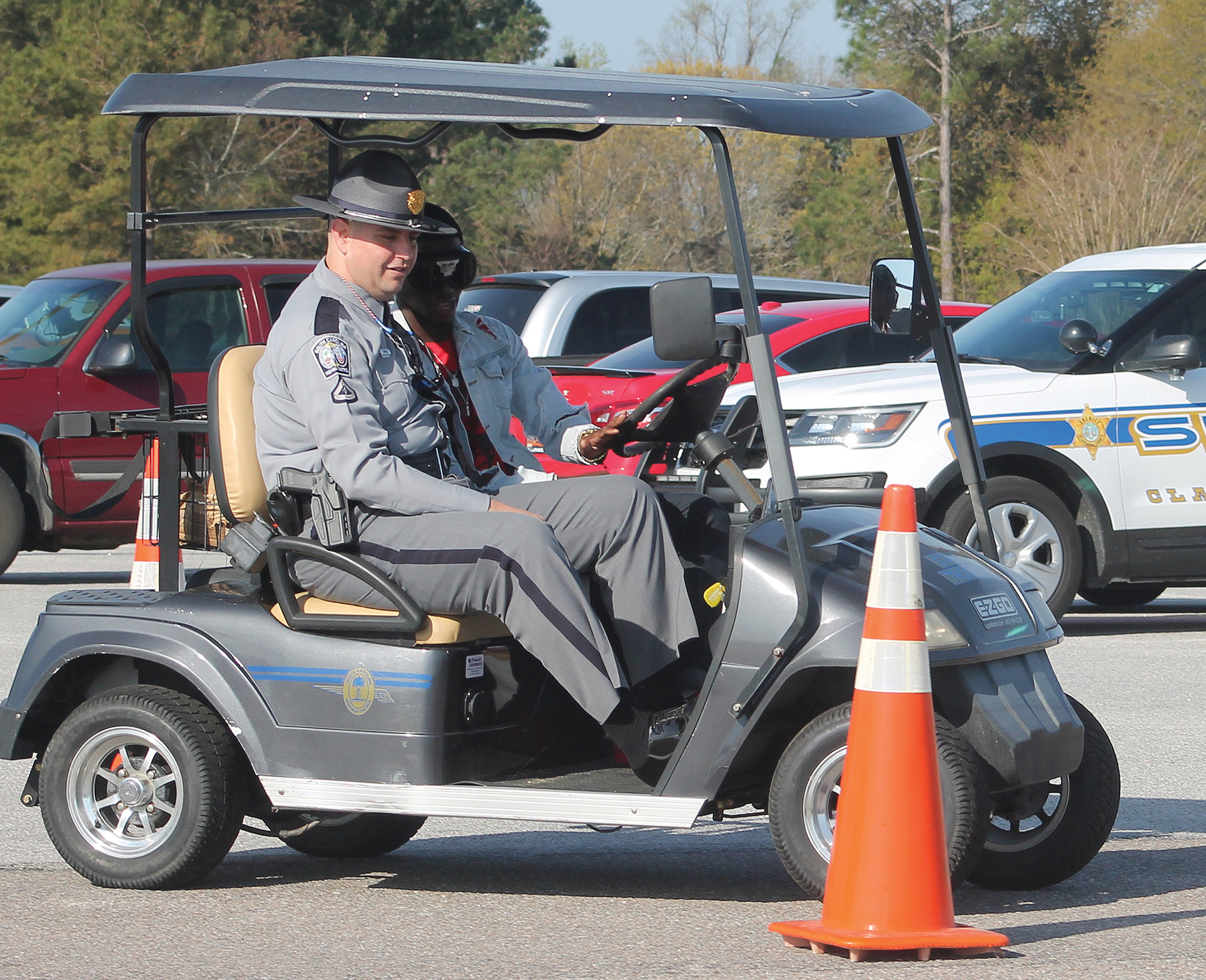 "Amonte Brown, a junior at Scott's Branch High School, drove through an obstacle course Wednesday morning as part of the school's Prom Promise program. Trooper David Jones with the South Carolina Highway Patrol, who is shown in the golf cart with Brown, had the student wear a pair of ""drunken"" goggles that would give the wearer the sense of being under the influence of alcohol at twice the legal limit. Brown couldn't maneuver around the obstacle course without driving outside the bounda"
