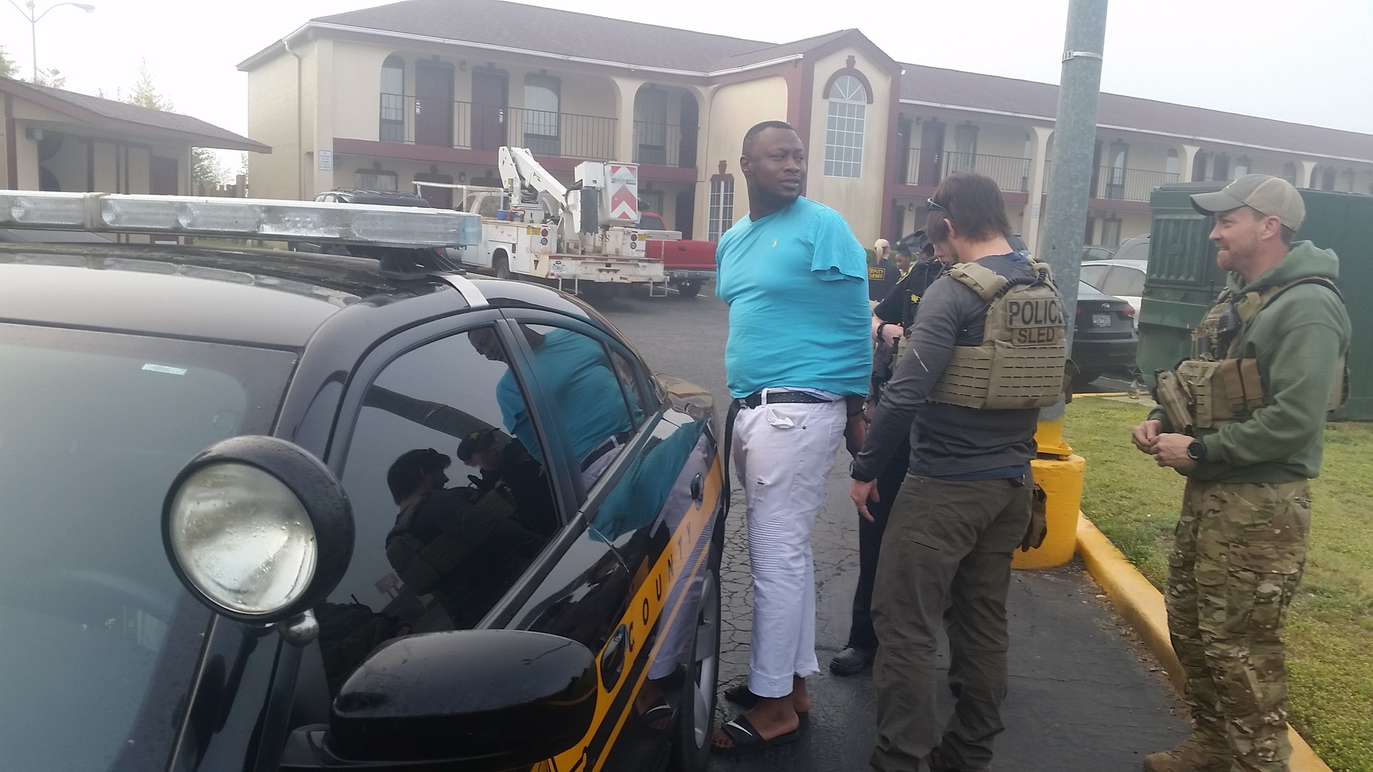 Travis Dunham is cuffed before being placed in the back of a patrol car at a motel on Tuesday morning.