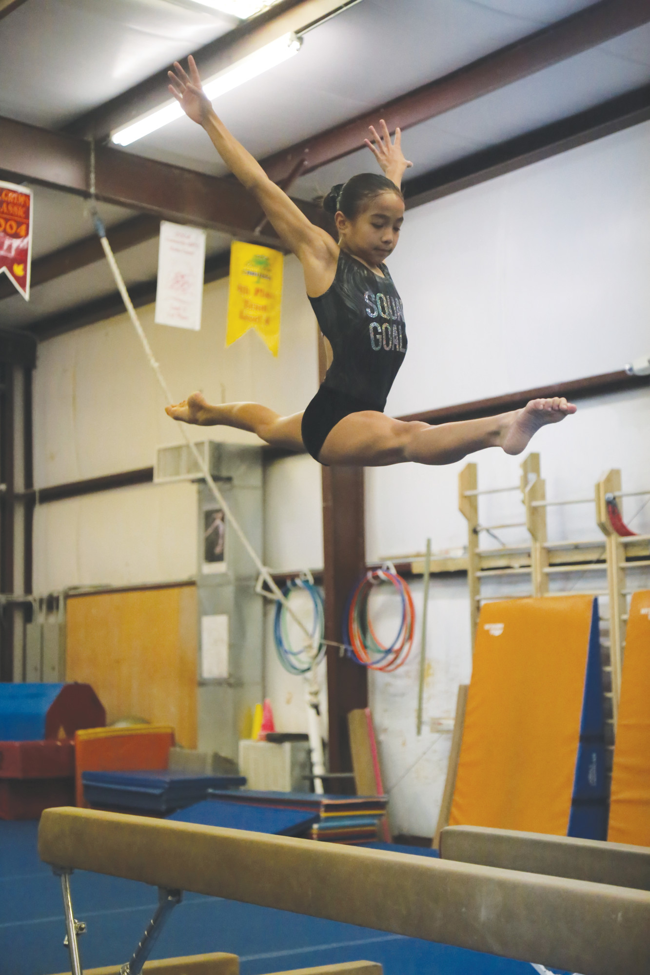 Mia Gabriel flies high above the beam during a recent practice session at Miss Libby's School of Dance and Gymnastics. Gabriel will compete in the Level 6 regional championships next weekend at the Classic Center in Athens, Georgia.